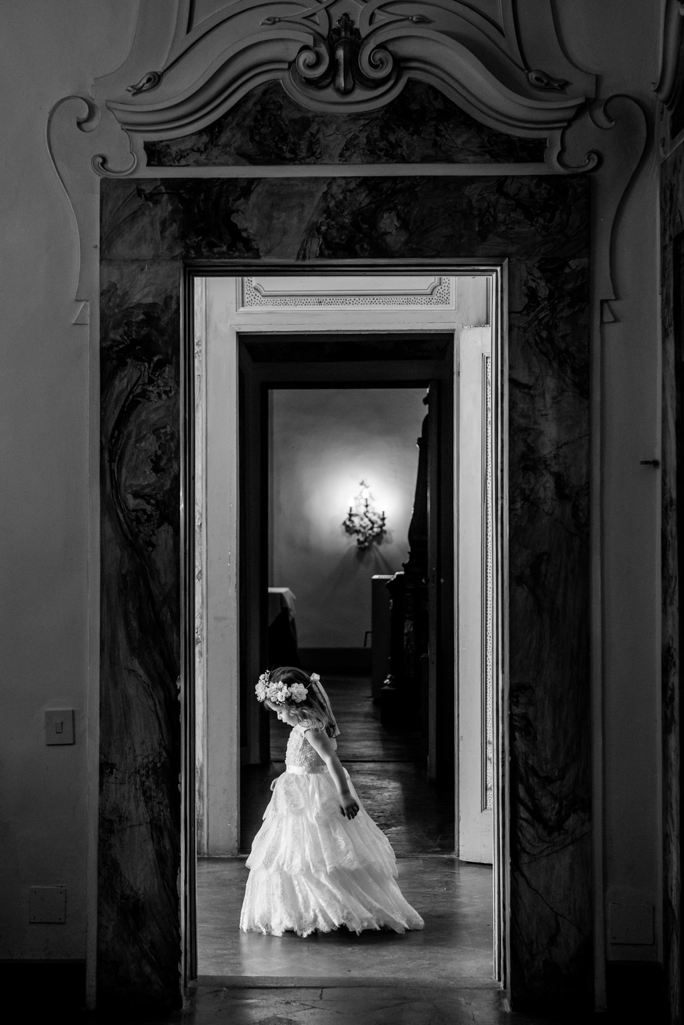 Little flowergirl framed in doorway by Morgan Lynn Razi