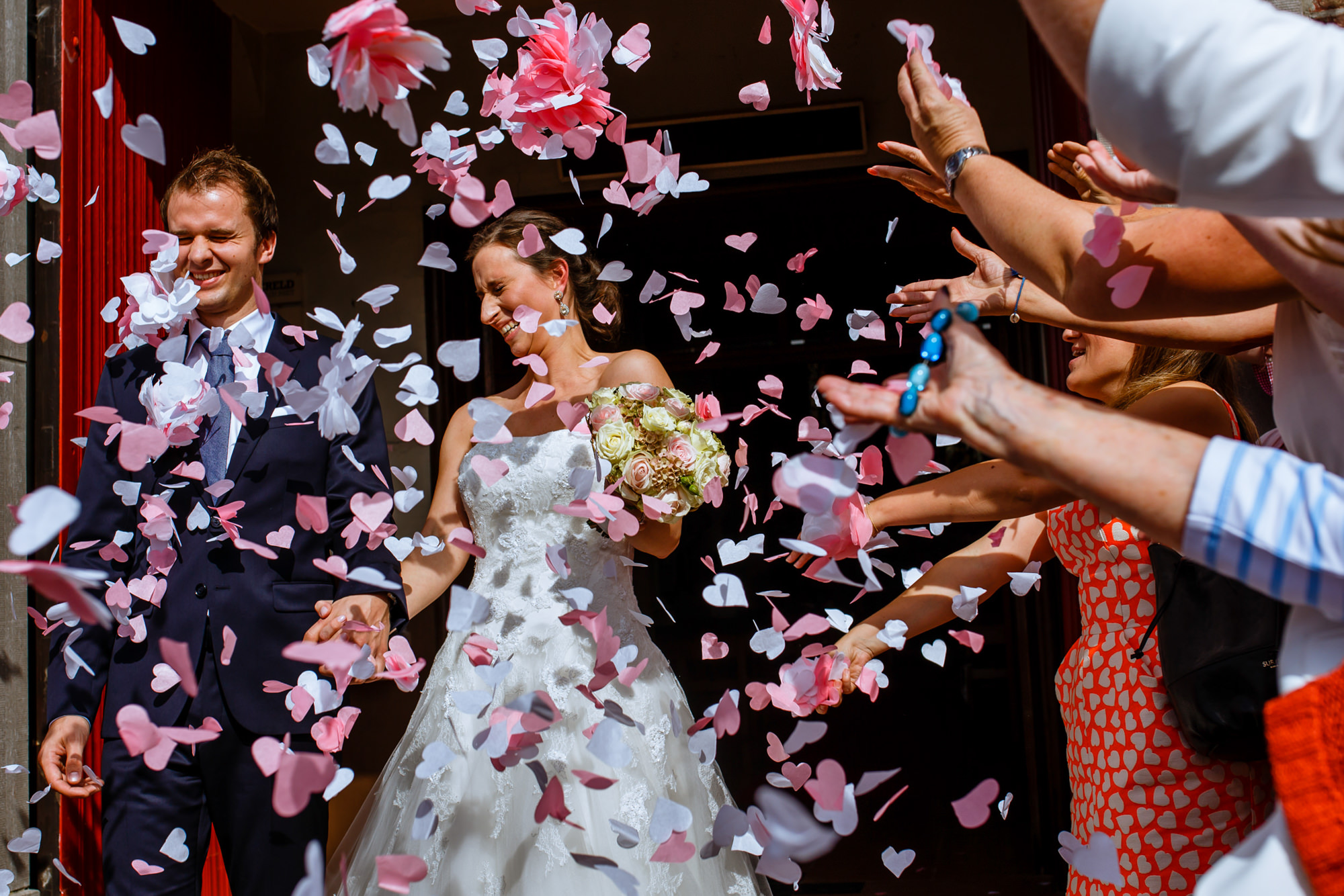 Confetti thrown on bride and groom exiting church - photo by Phillipe Swiggers
