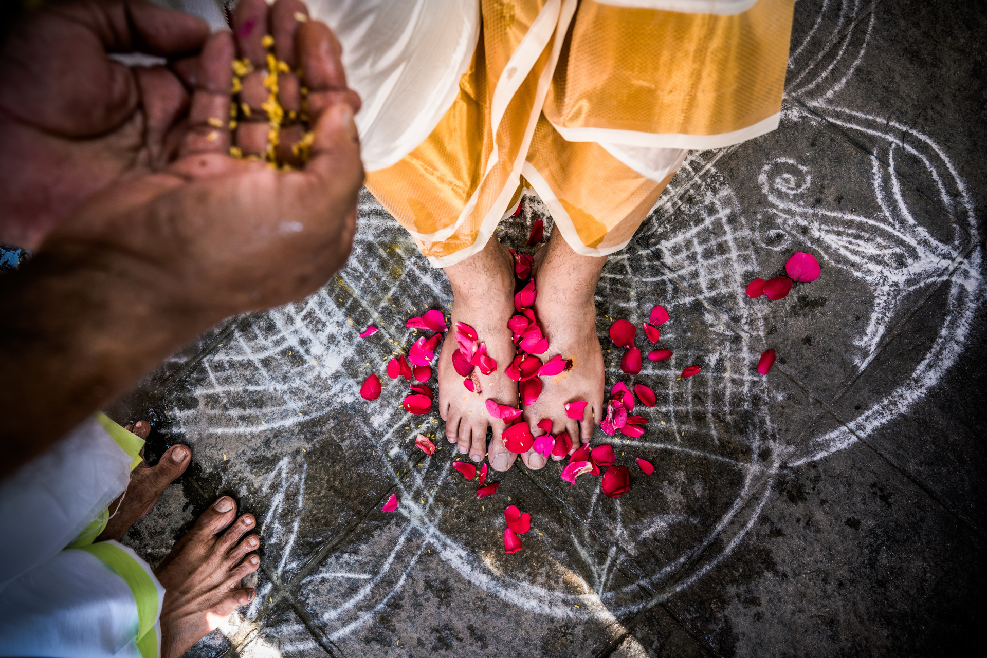 Red rose petals around grooms feet - photo  by Sephi Bergerson