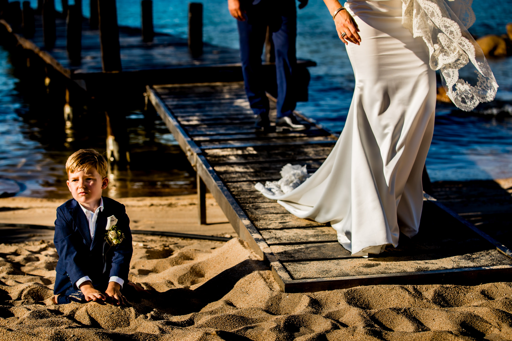 Ring bearer buries himself in the sand - photo by Eppel Photography