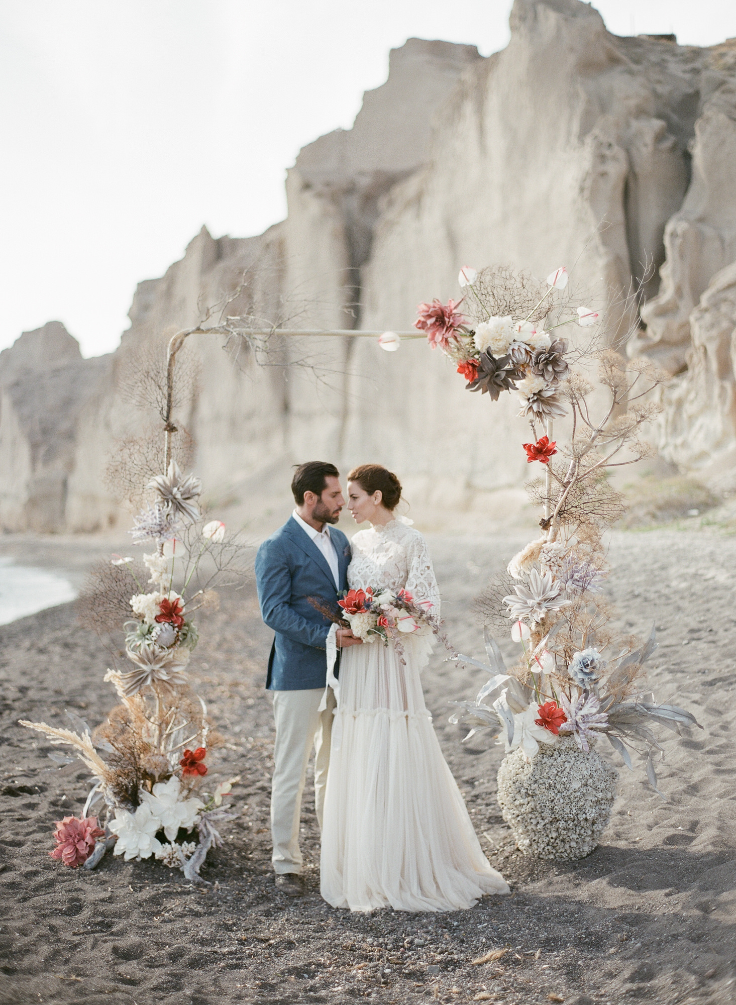 Couple under floral arbor on beach  - photo by Gianluca Adovasio Photography