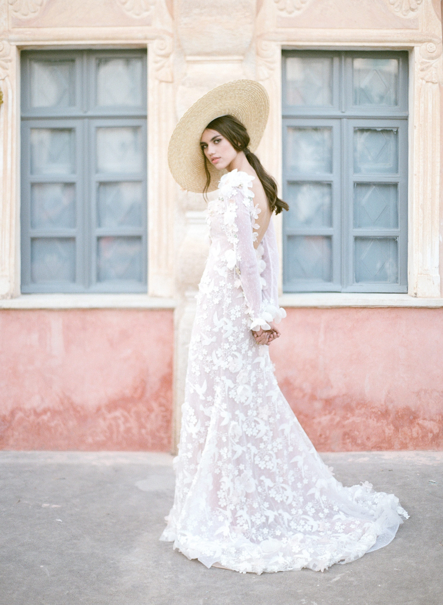Bride in lace applique dress with large straw hat - photo by Gianluca Adovasio Photography