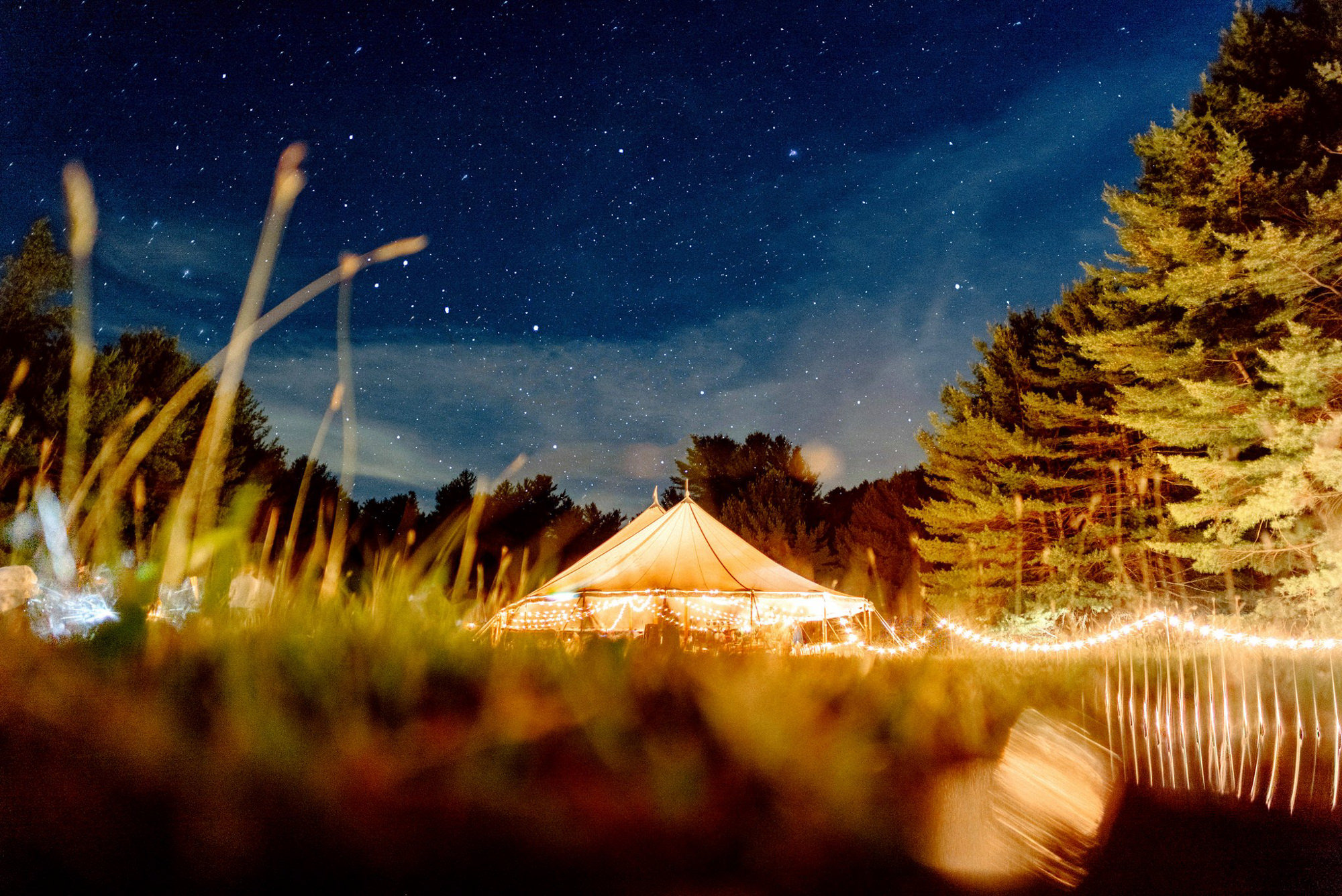 Lighted tent reception with stars above - Photo by Benj Haisch