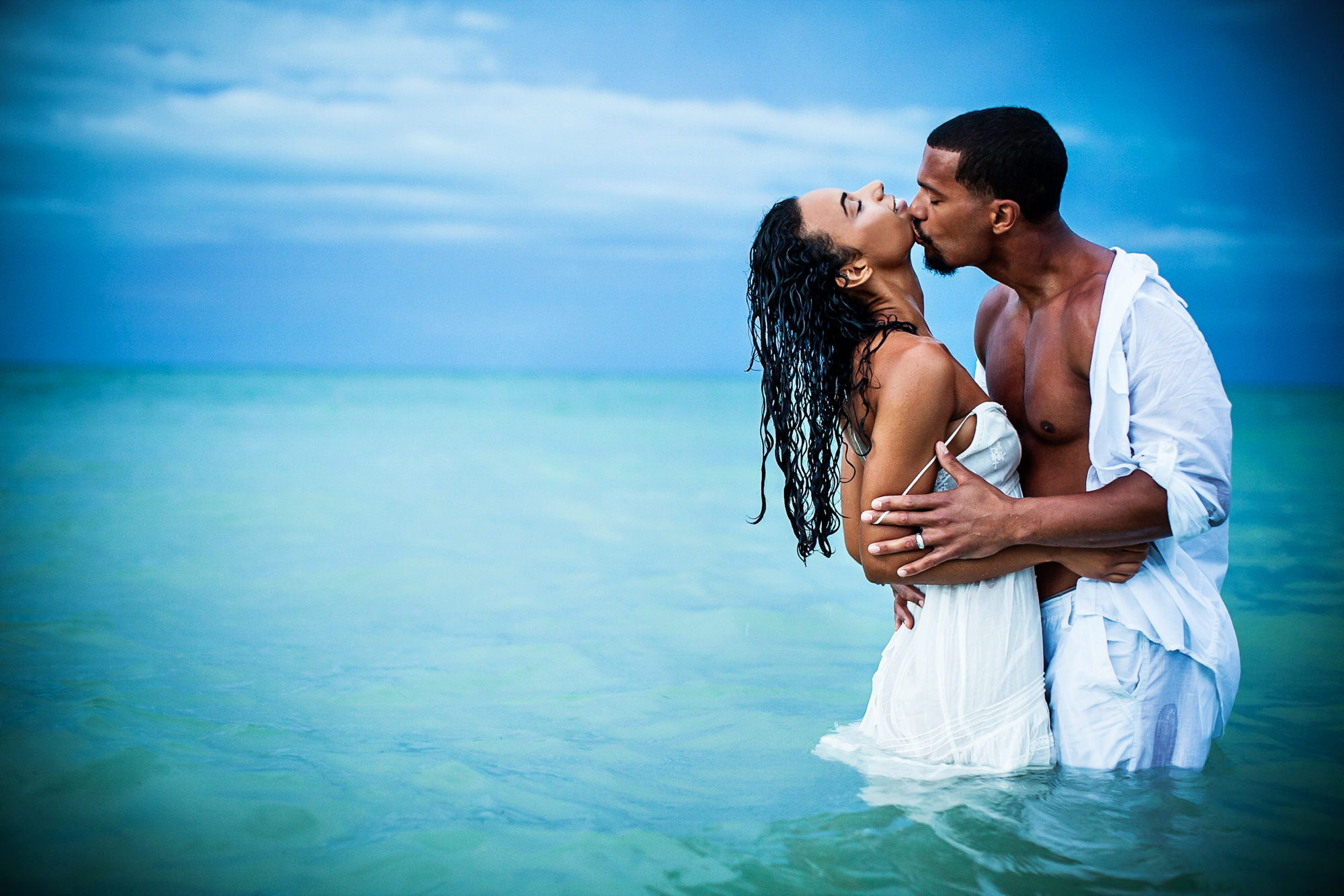 Sensual portrait of bride and groom kissing in water - photo by Jag Studios