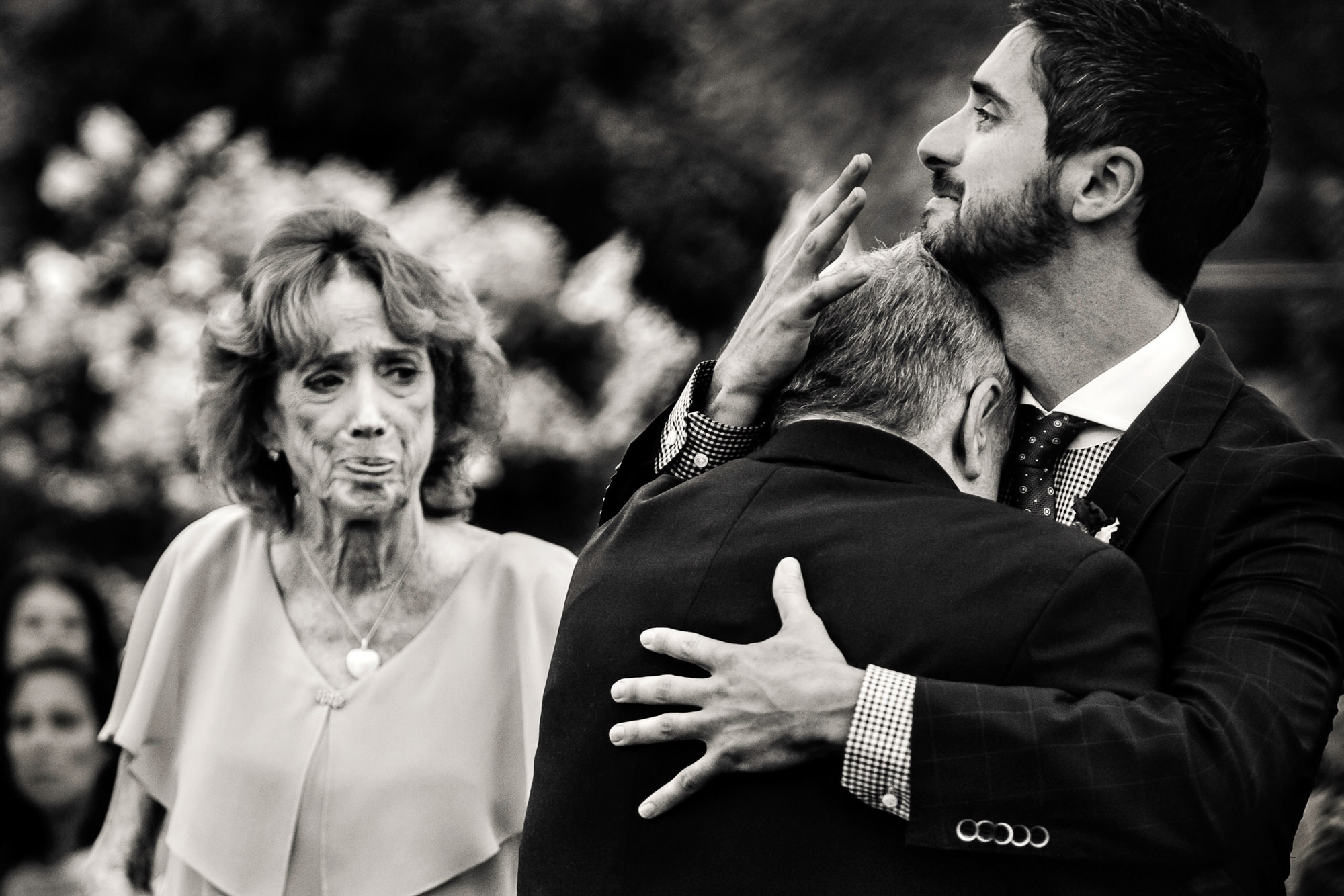 Father cries on grooms shoulder while mom looks on - photo by Jag Studios