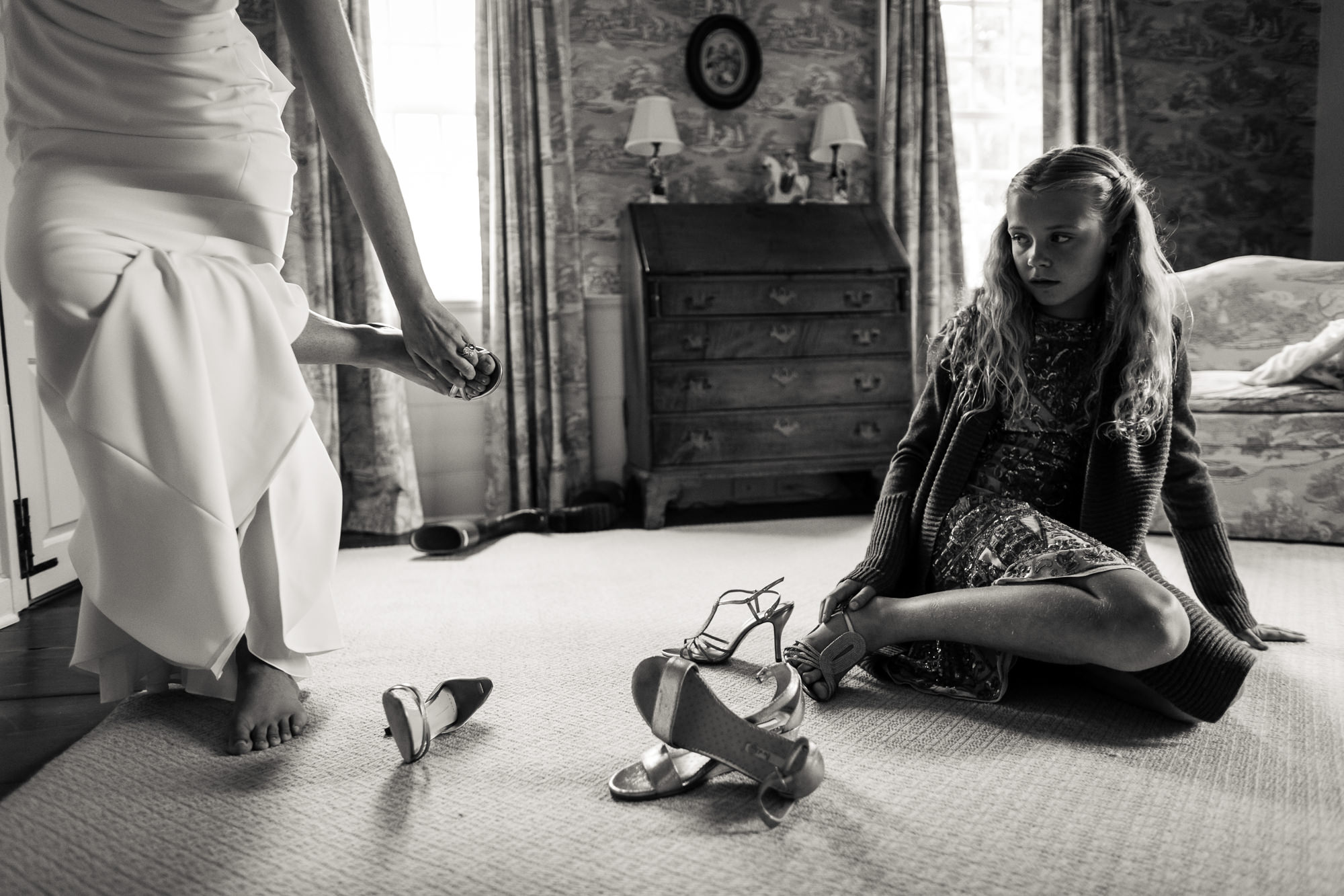Young girl watches bride put her shoes on - photo by Jag Studios