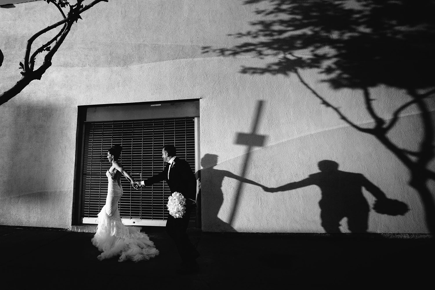 Bride and groom in low evening light with a cross shadow, by Callaway Gable