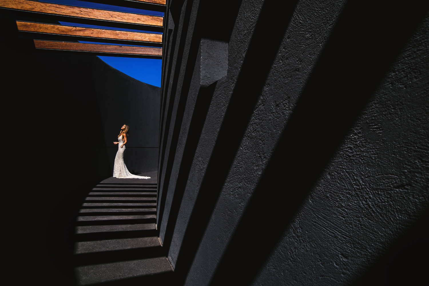 Creative bridal portrait along curved wall with light and shadows, by Callaway Gable