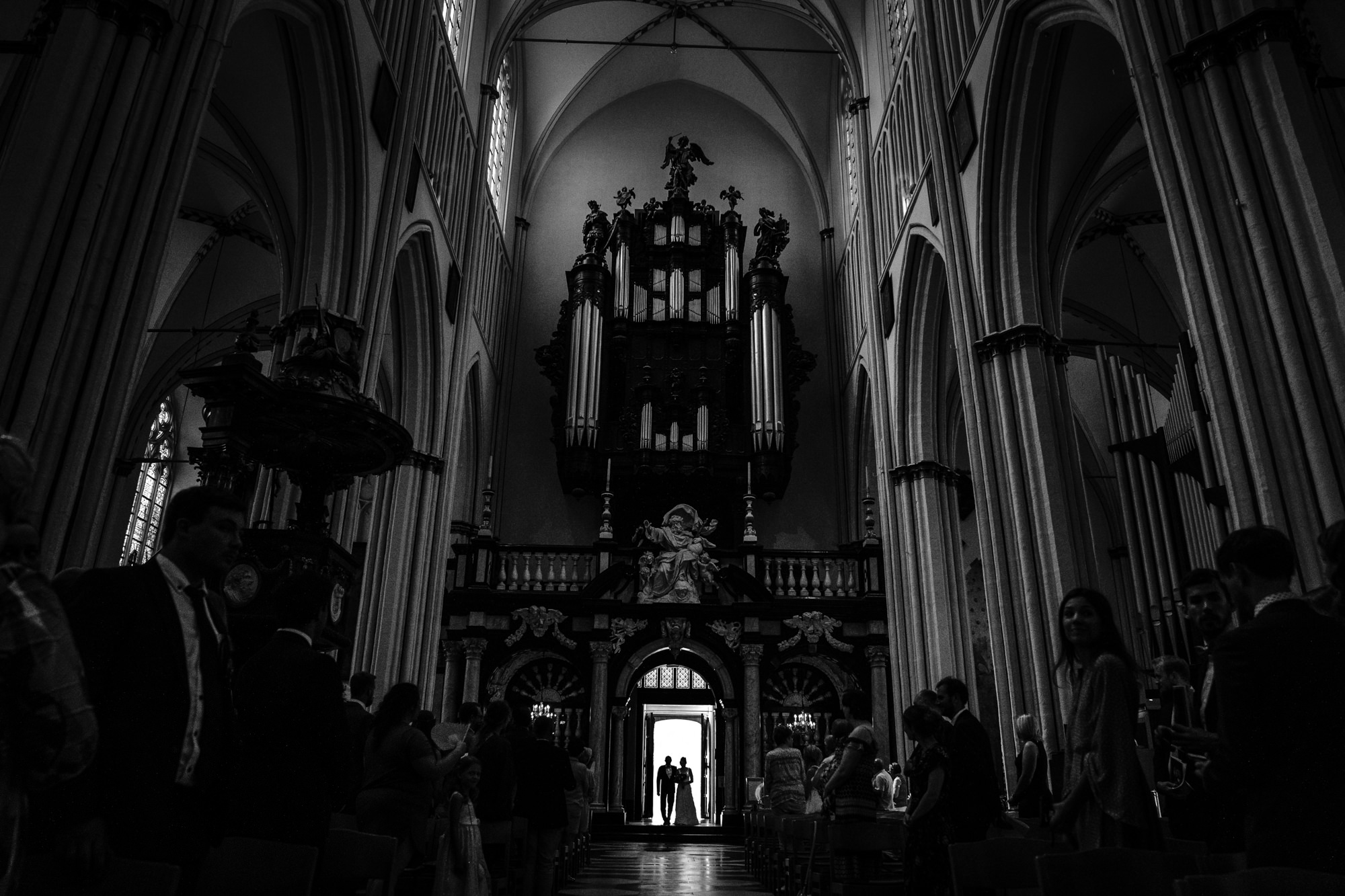 Silhouette of bride and father at cathedral doors, black and white photo by Yves Schepers, Belgium wedding photographers