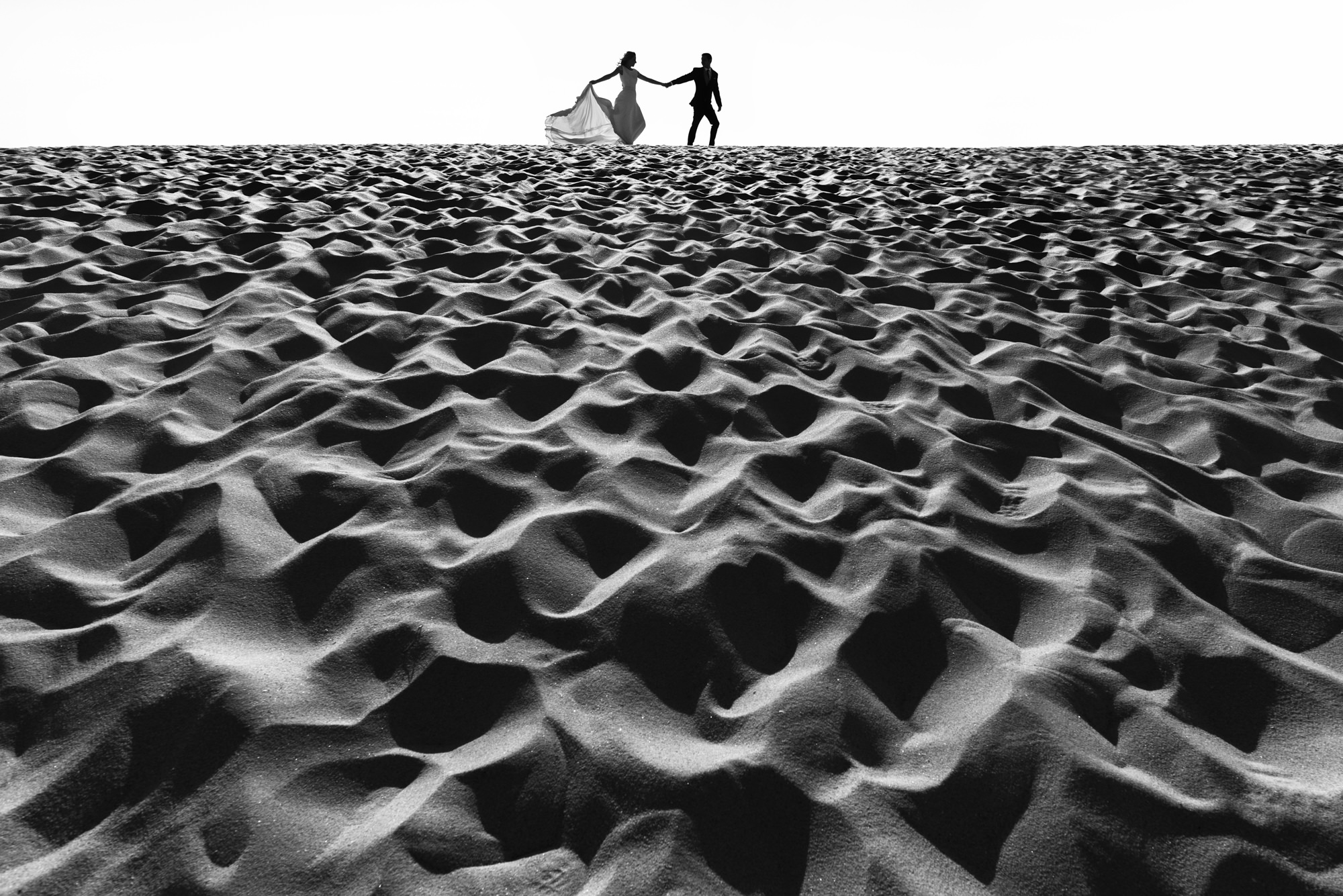 Silhouette of bride and groom running along sand - photo by Look Fotographica