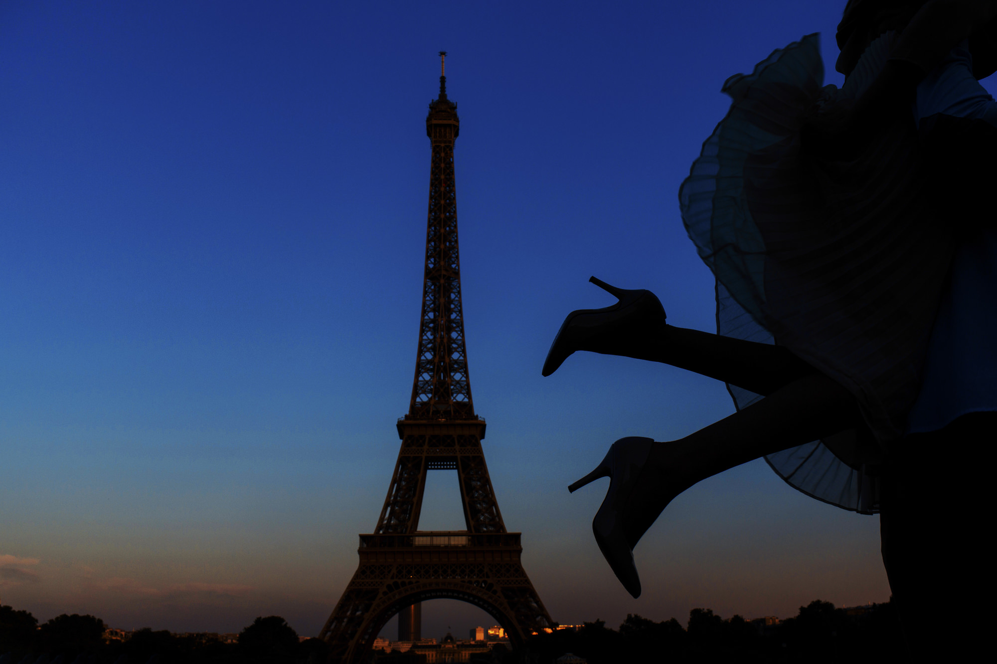 Silhouette of bride kicking up stiletto heels at eiffel tower in paris - photo by Look Fotographica