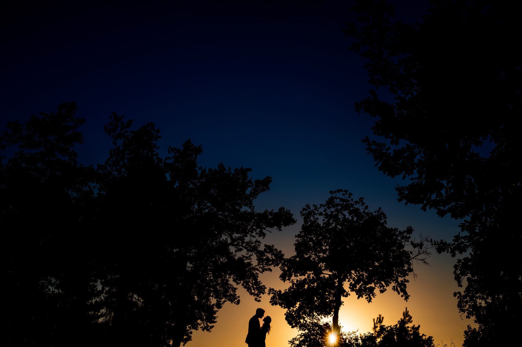 couple silhouette under darkening sky - photo by Cooked Photography