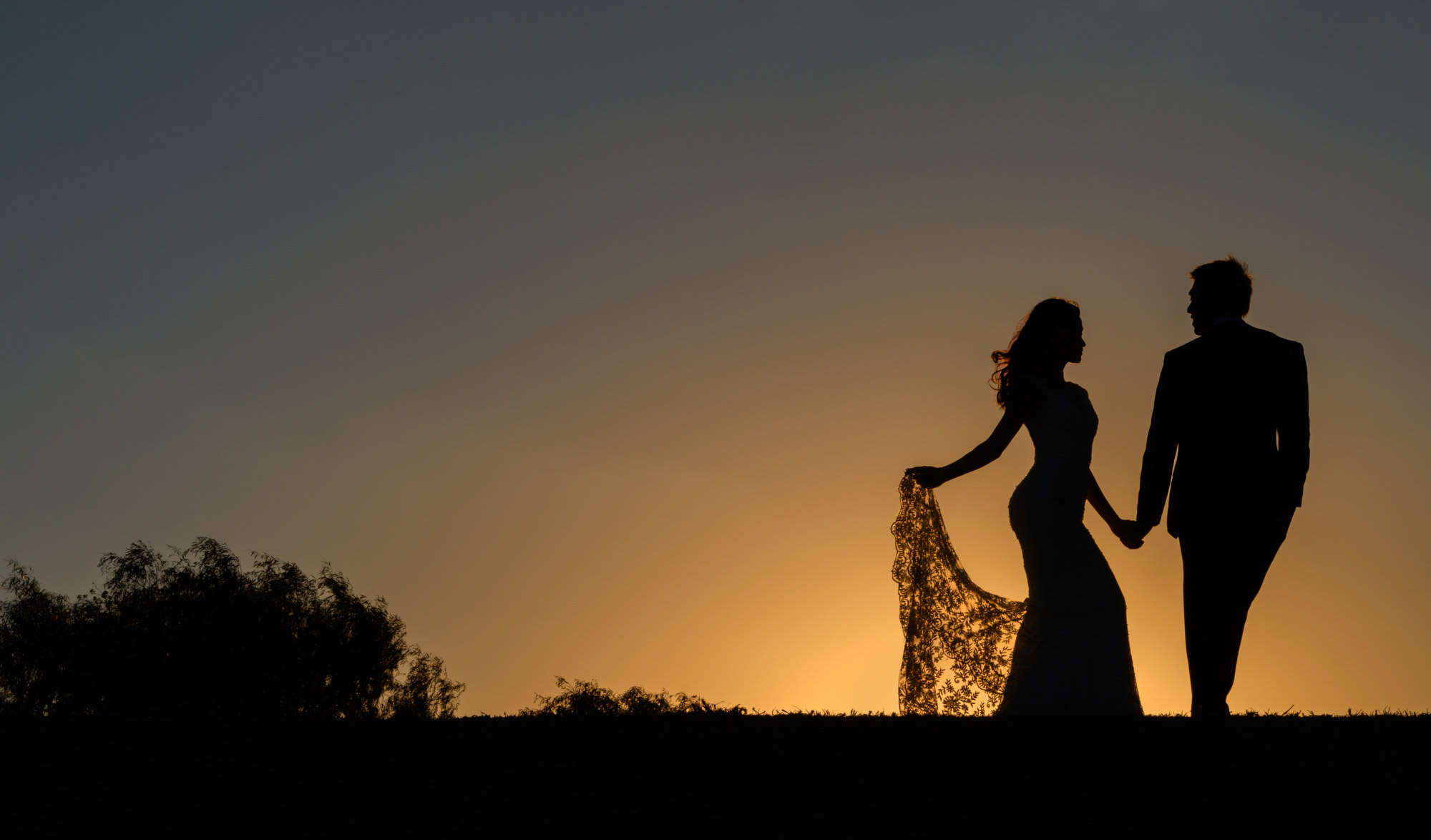 Silhouette photo of couple at sunset - photo by Jerry Ghionis