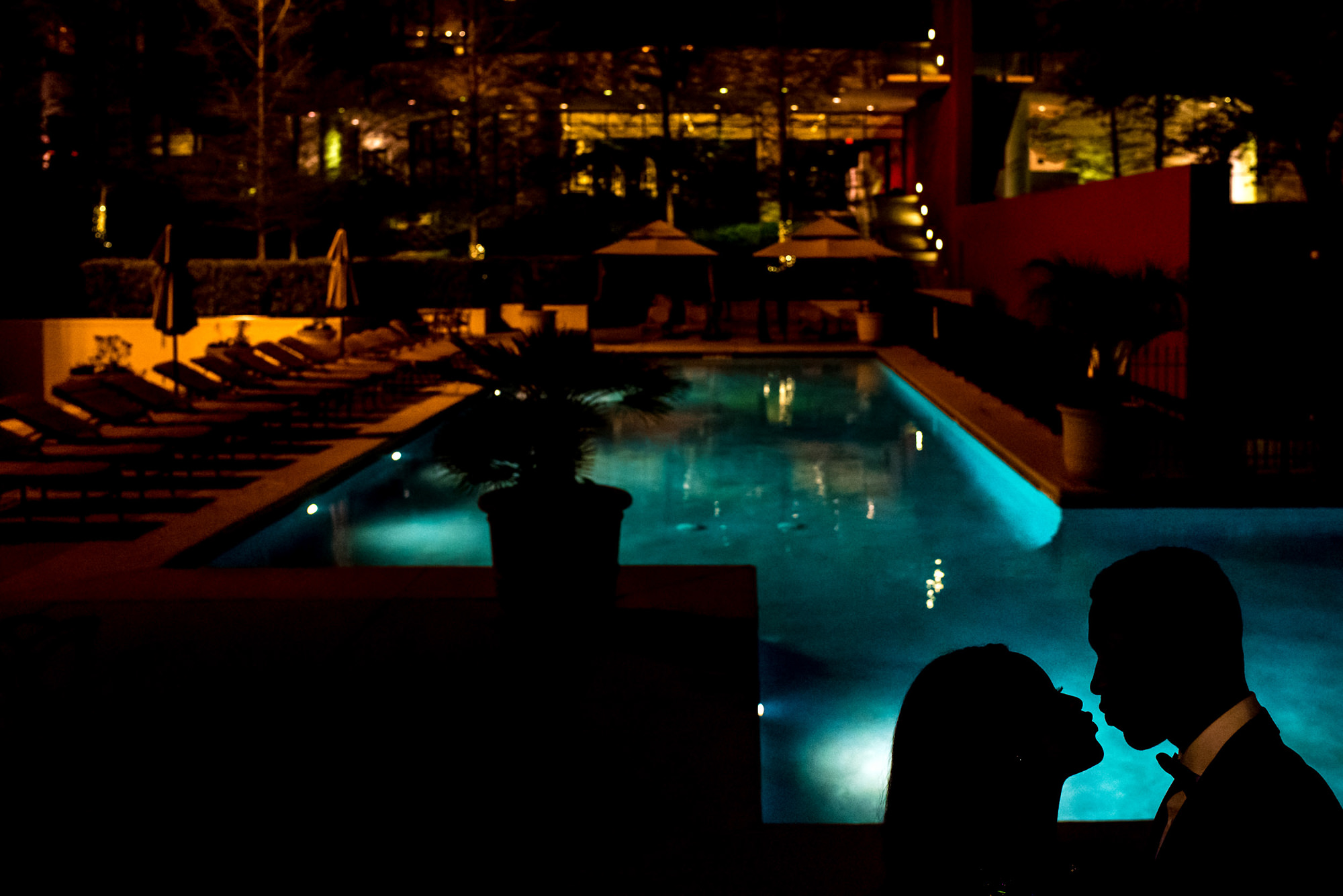 Couple silhouette by pool at night - photo by Alakija