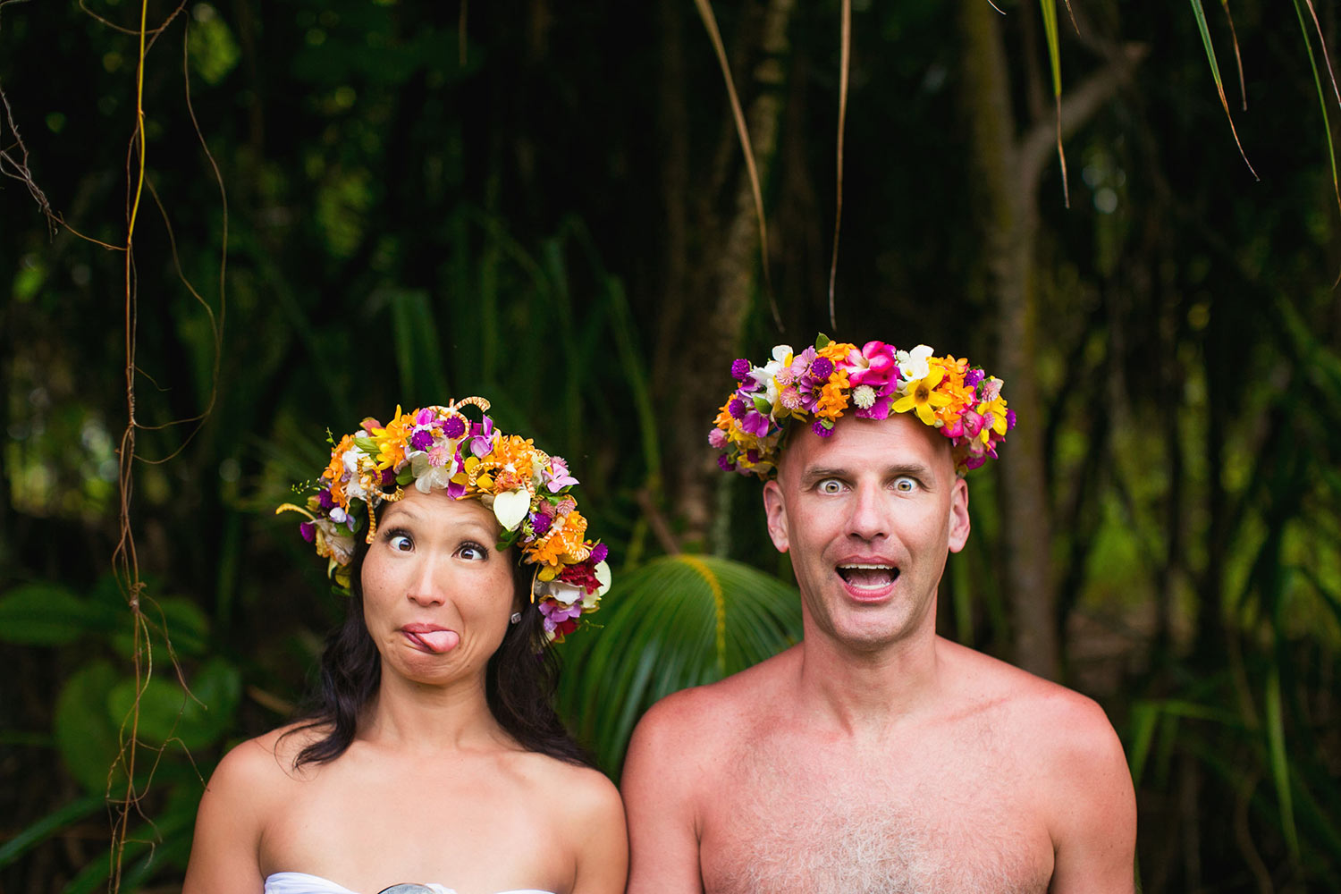 Silly portrait of couple in tropical floral crowns, by Callaway Gable