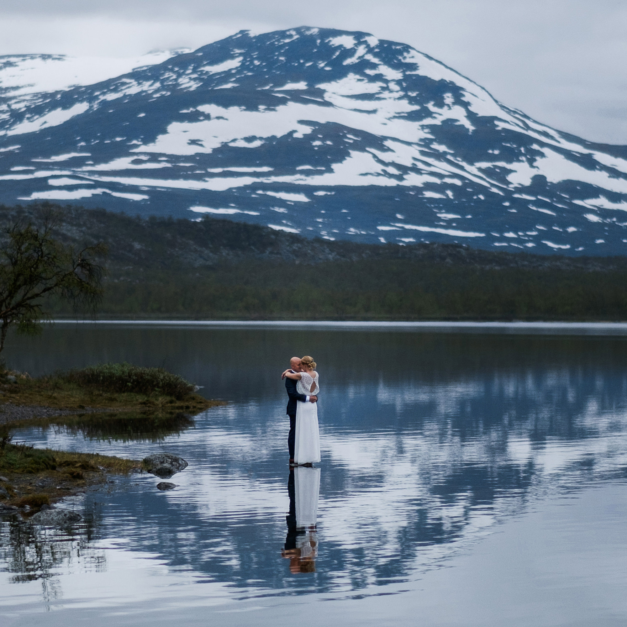 Couple embracing against mountain with reflection photo by Nordica Photography