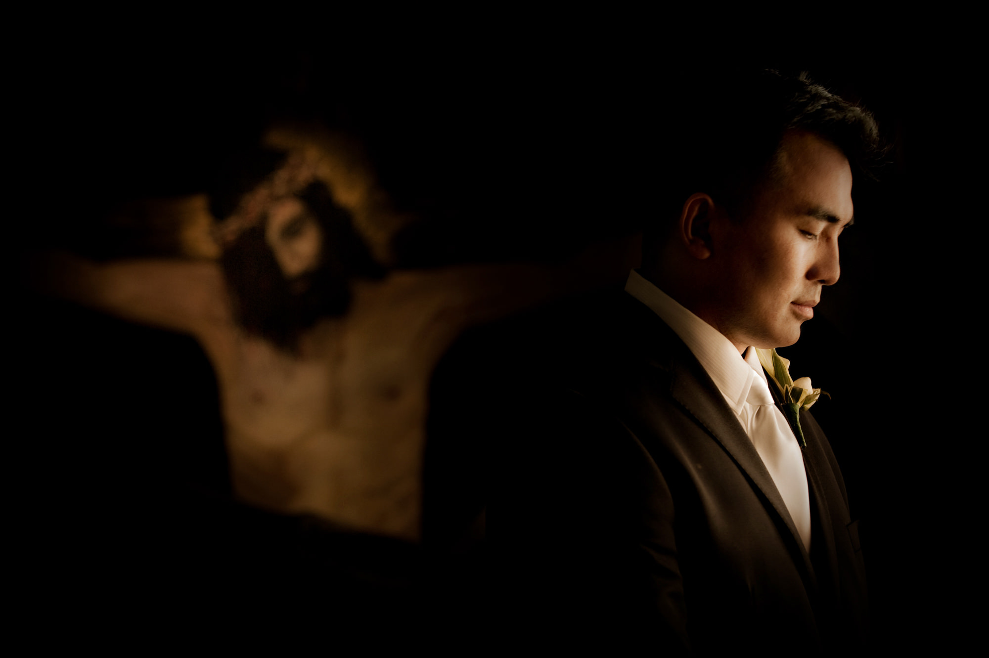 Soft portrait of groom's profile with jesus in backgroundphoto by Cliff Mautner