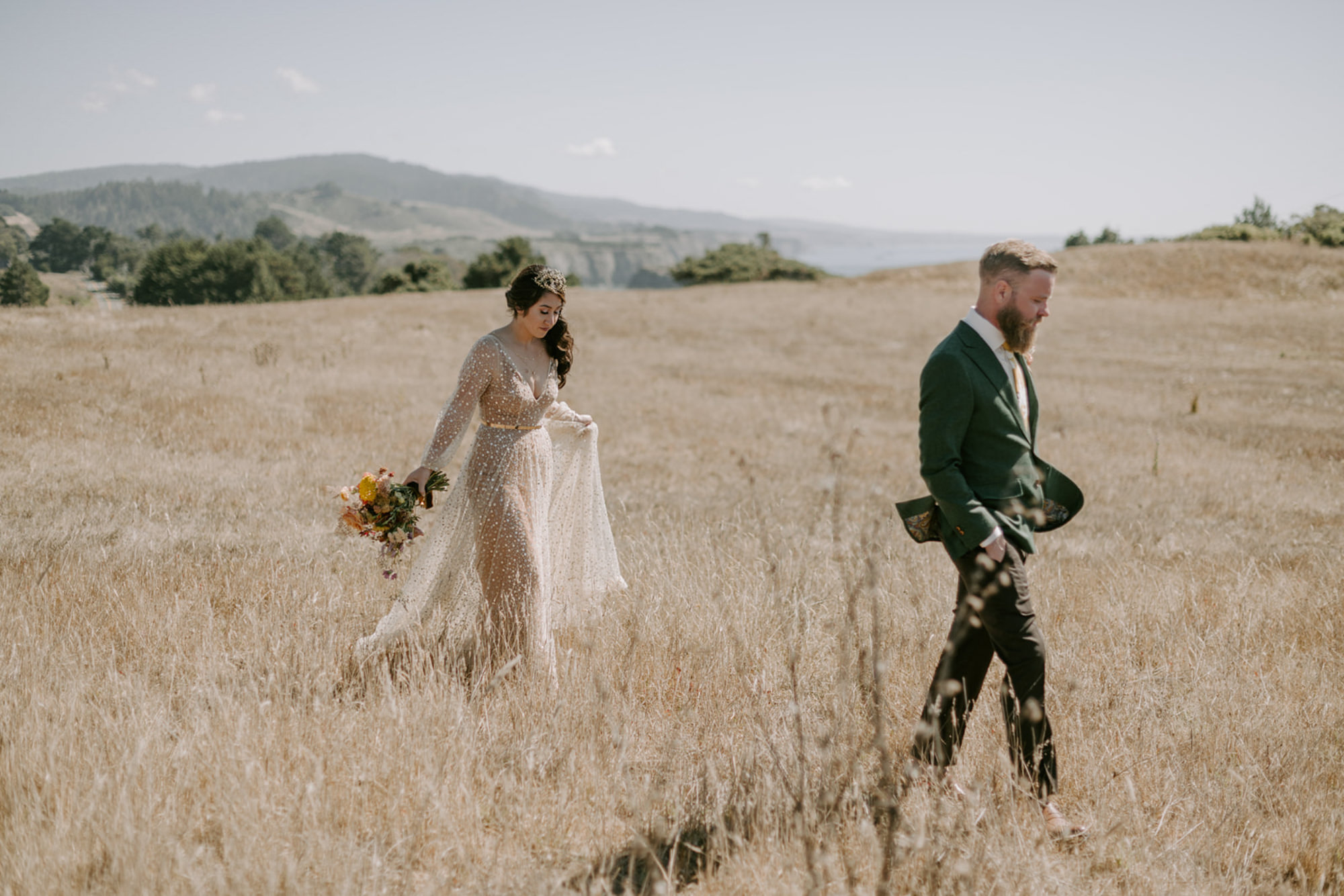 Bride in sparkle taupe plunging dress walking with groom in field - photo by Kri
