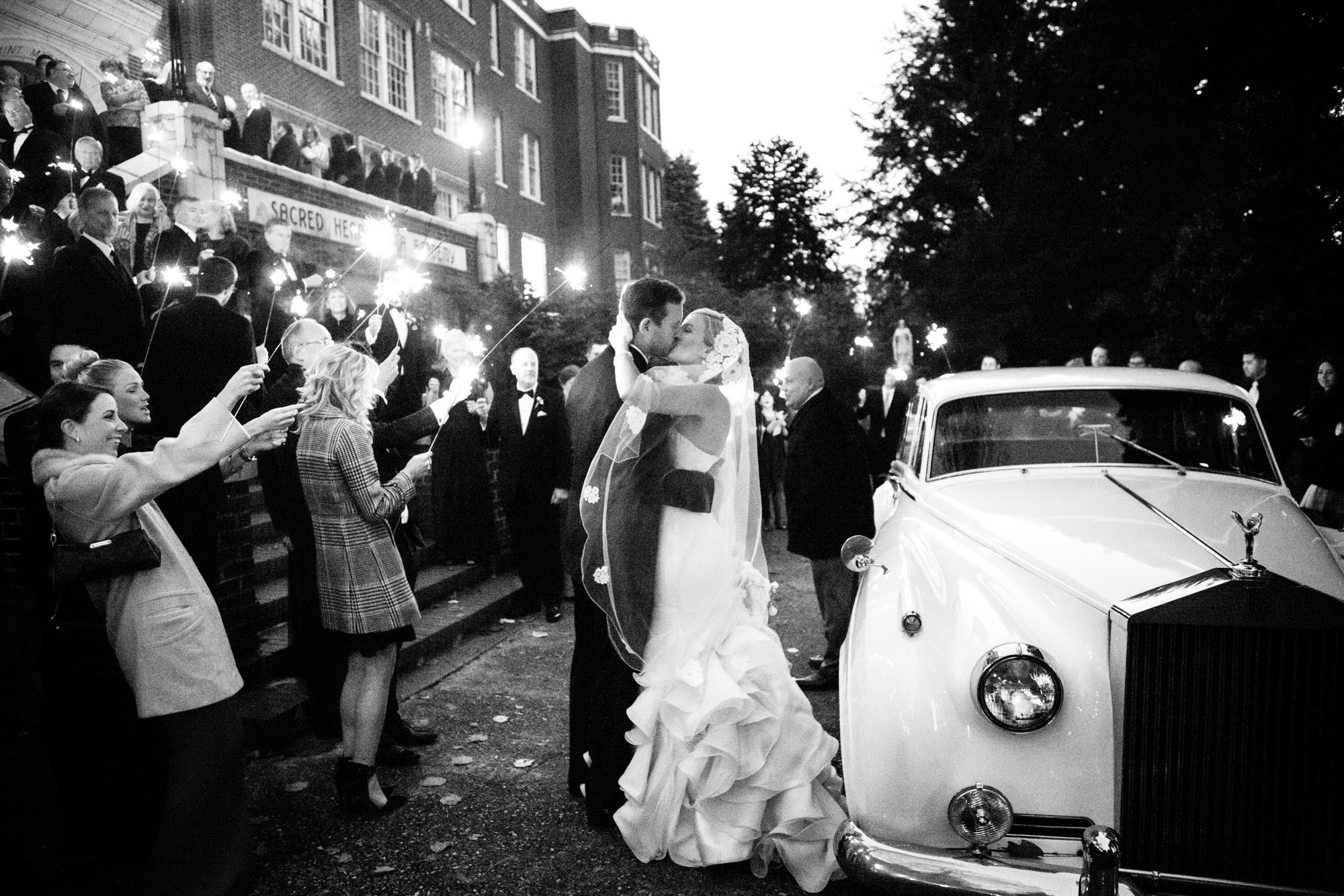 Couple kissing outside of church with guests holding sparklers  - La Vie Photography