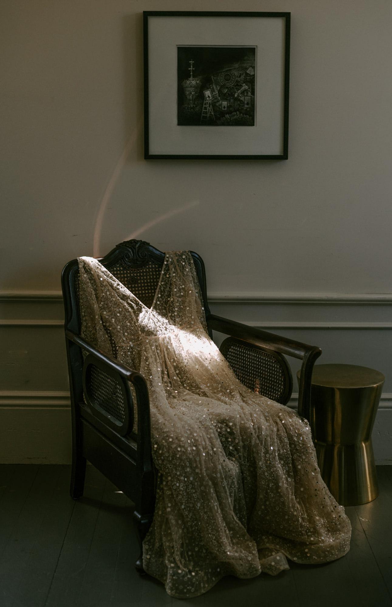 Sparkley wedding dress laying in windowlight - photo by Kristen Marie Parker