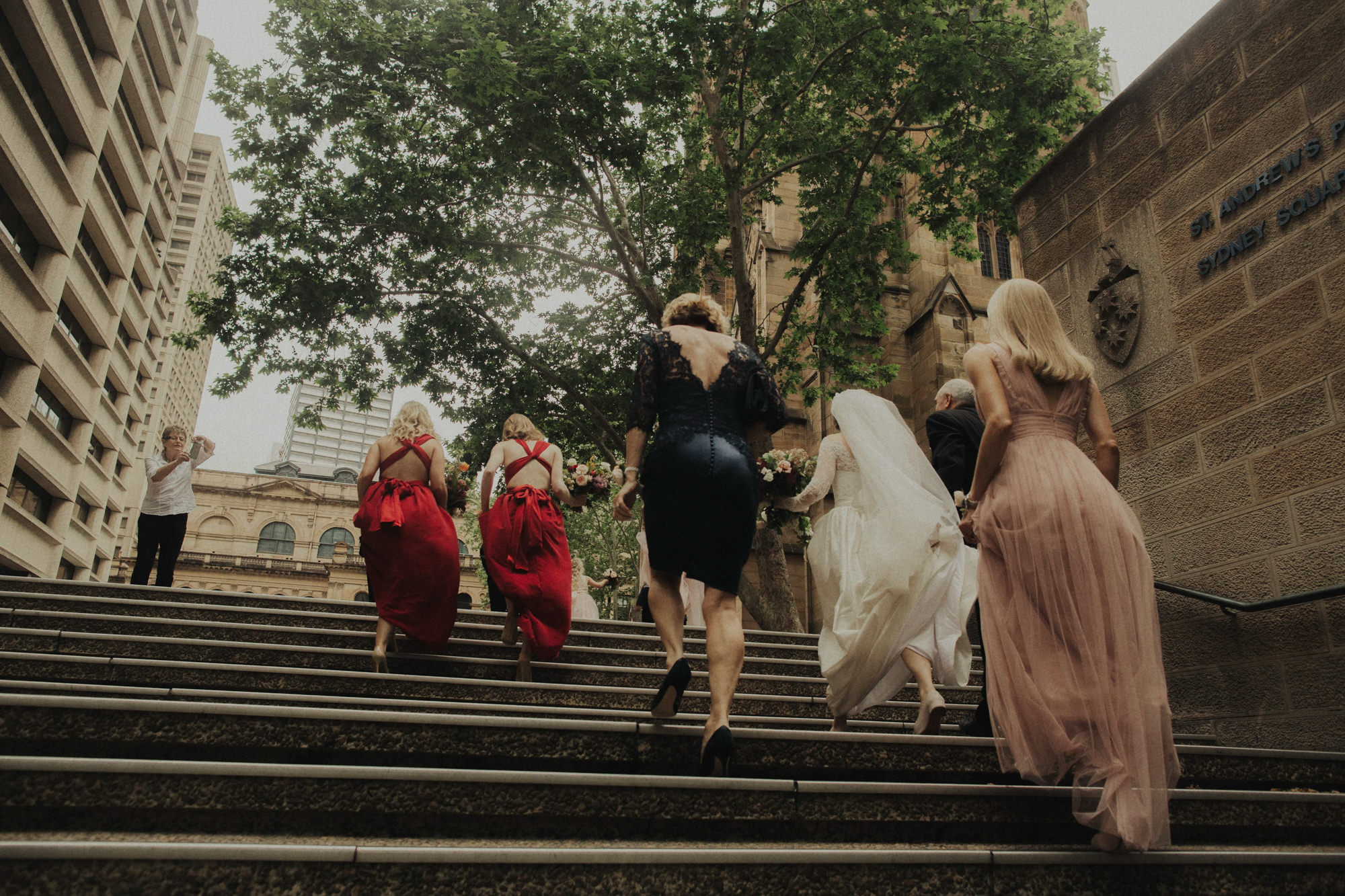 Stranger taking photo of bridal party ascending stairs - photo by Dan O'Day