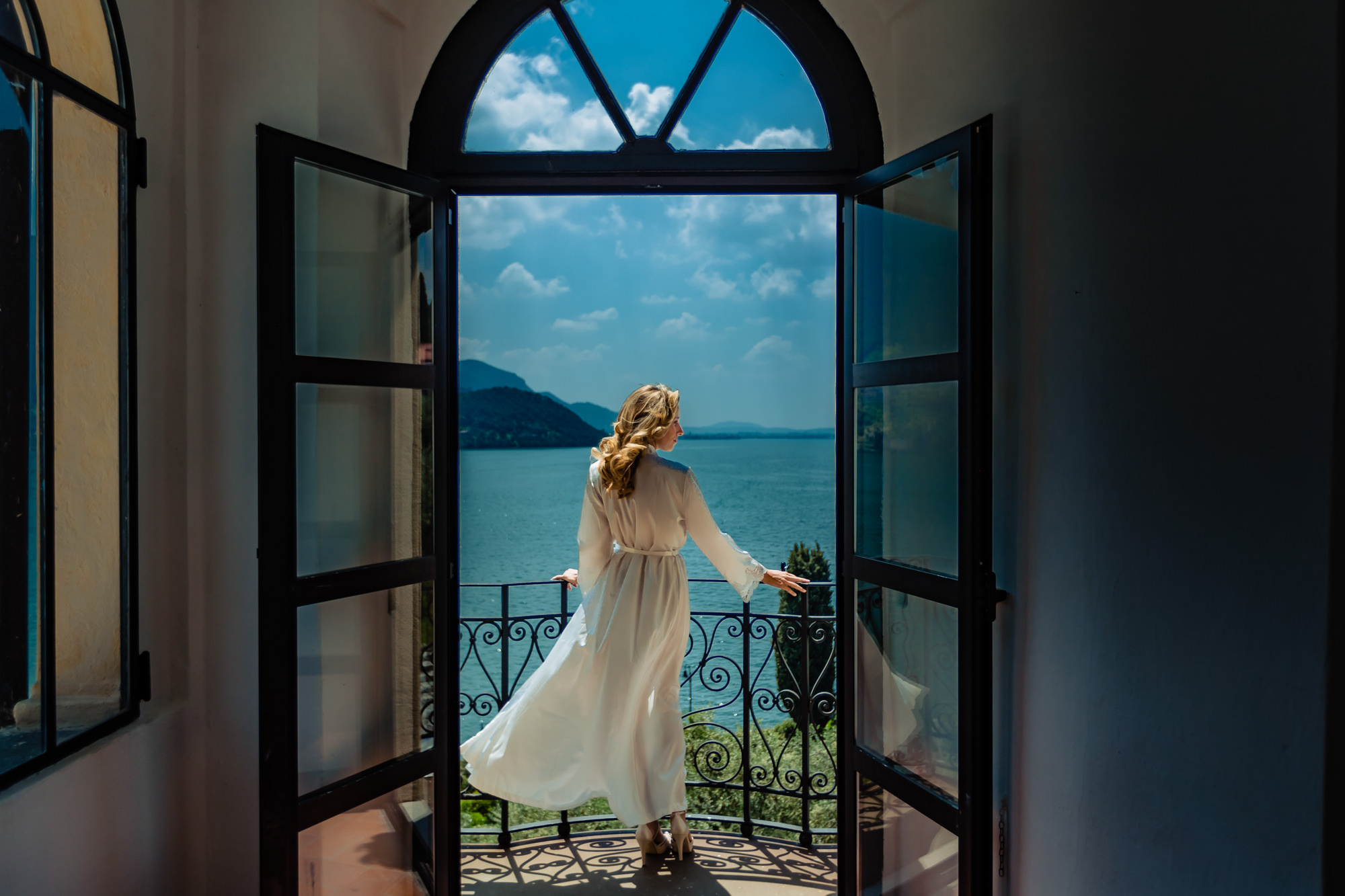 Bride by Lake Como in flowing robe by Eppel Photography Netherlands