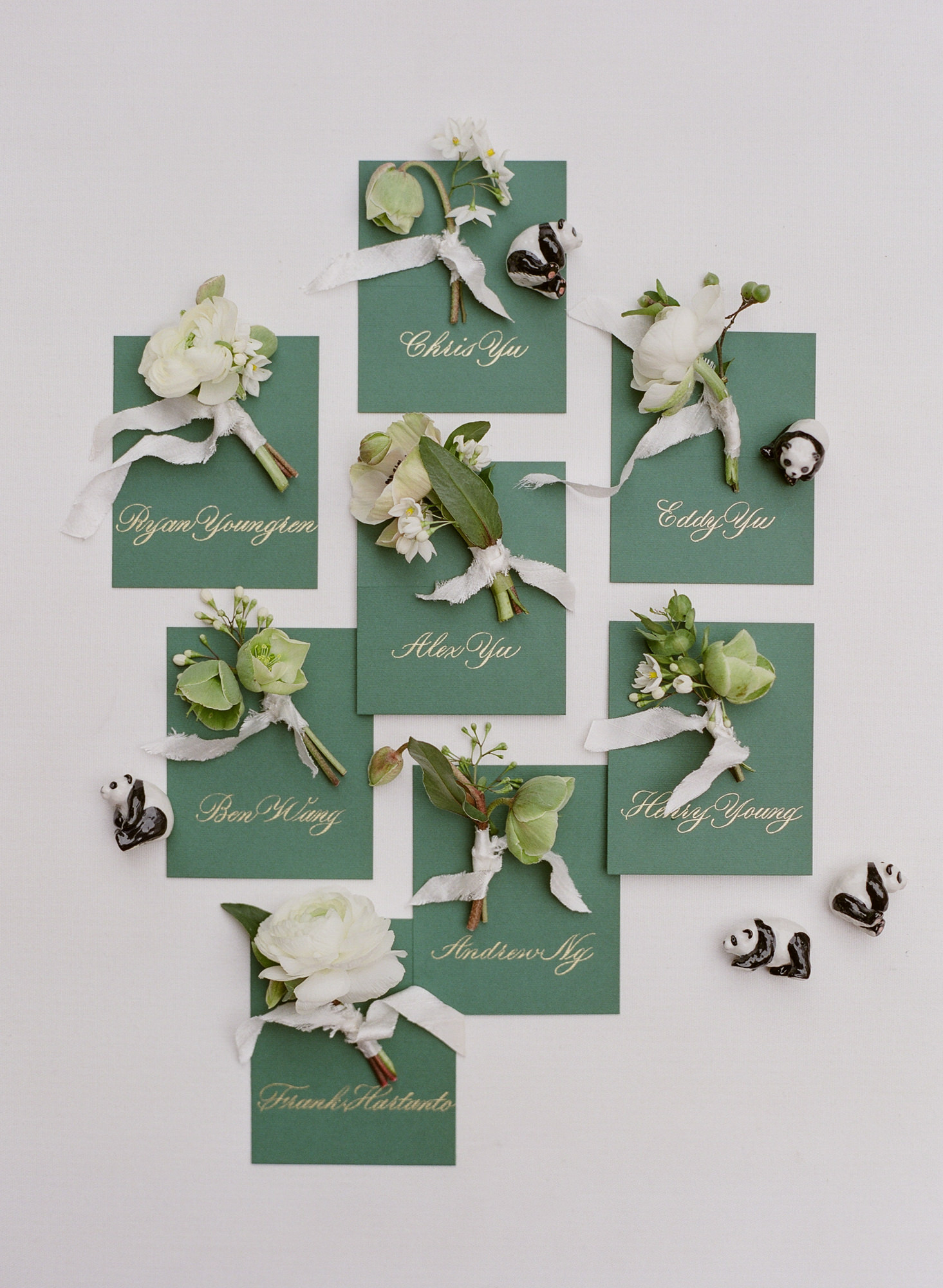 Flatlay of sage name cards with spring boutonnieres - Greg Finck Photography
