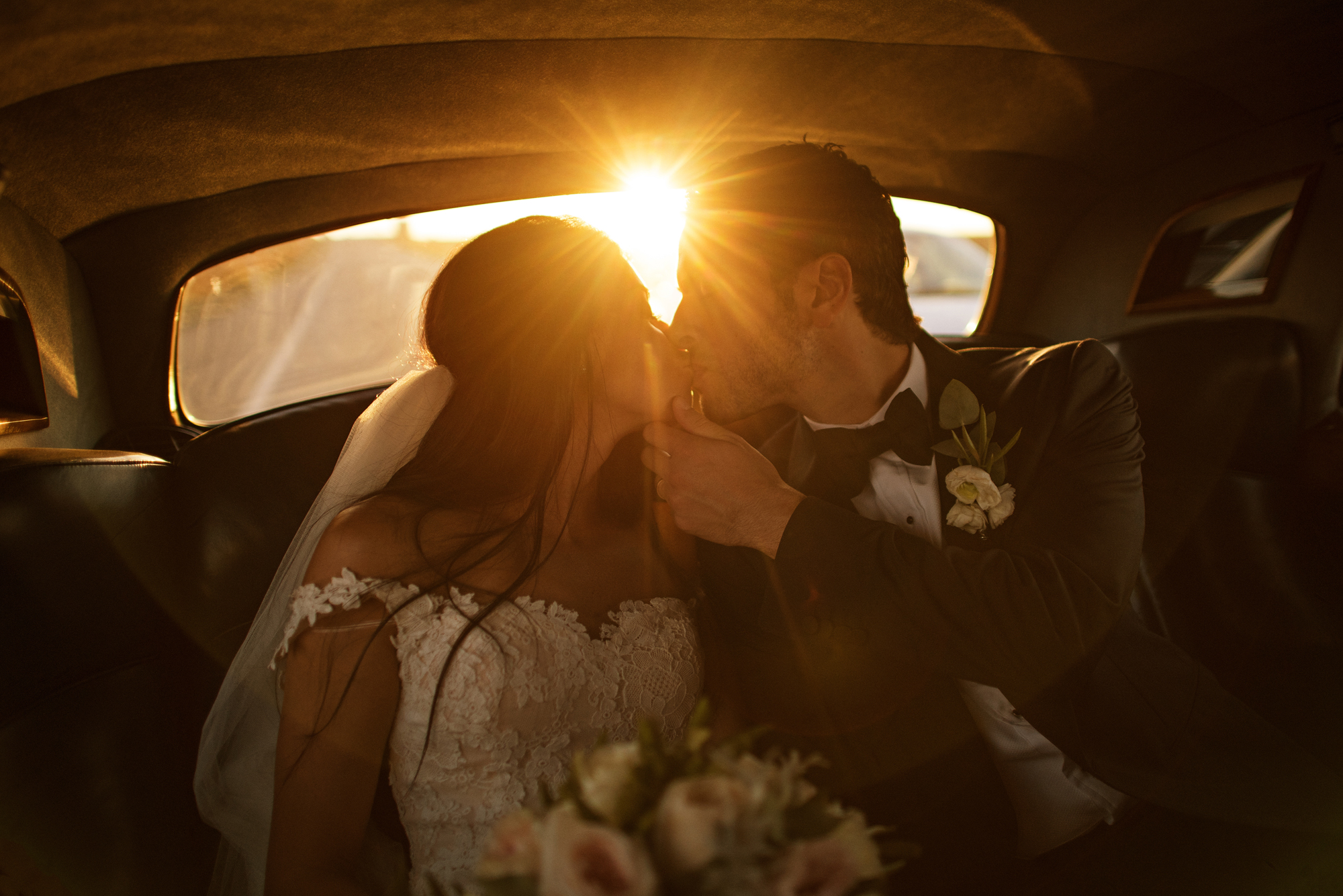 Couple kissing in limo at sunset - photo by Cooked Photography
