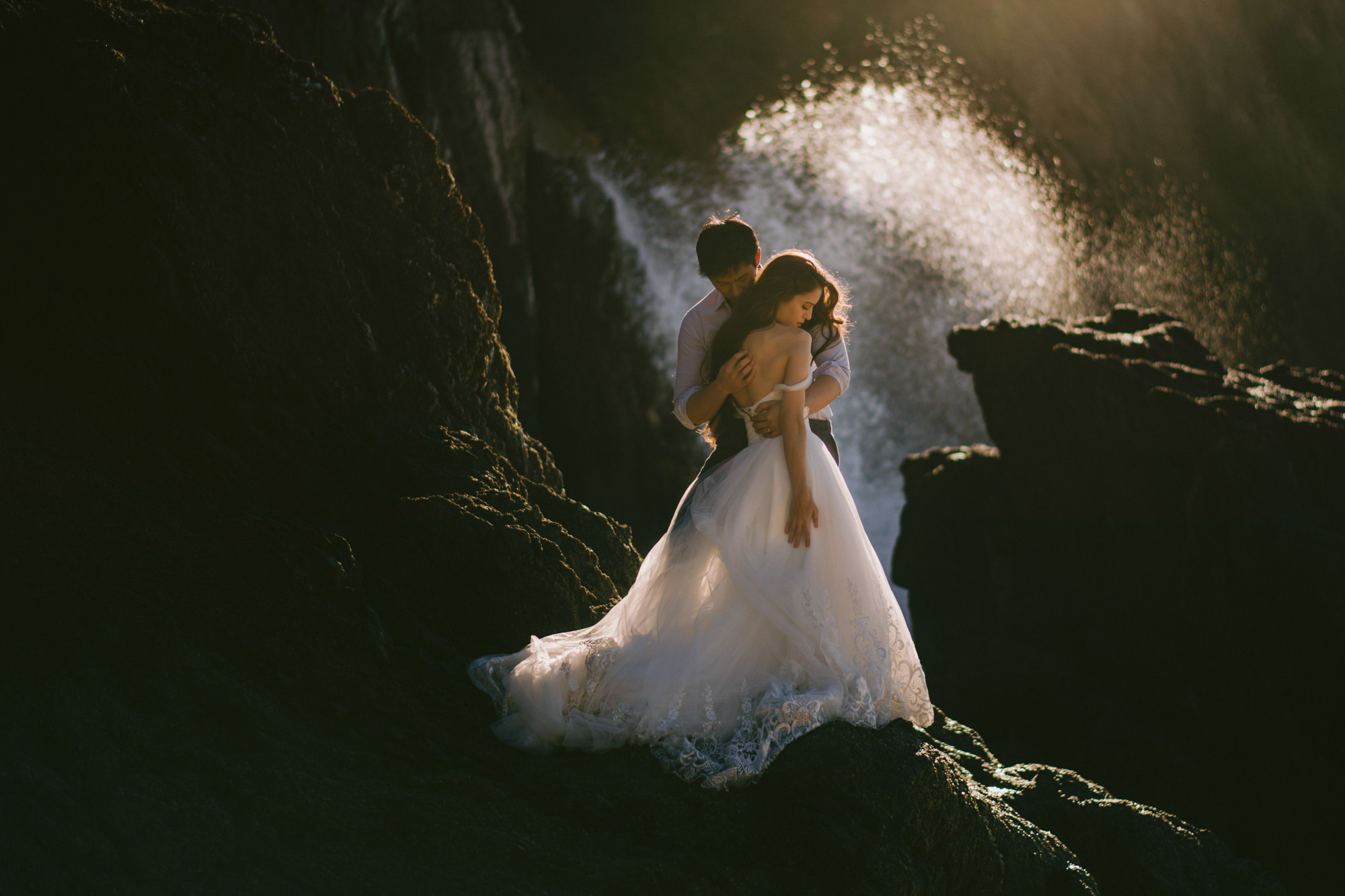 Surf crashes behind couple - bride in low back chiffon ballgown -photo by McClintock Photography Agency