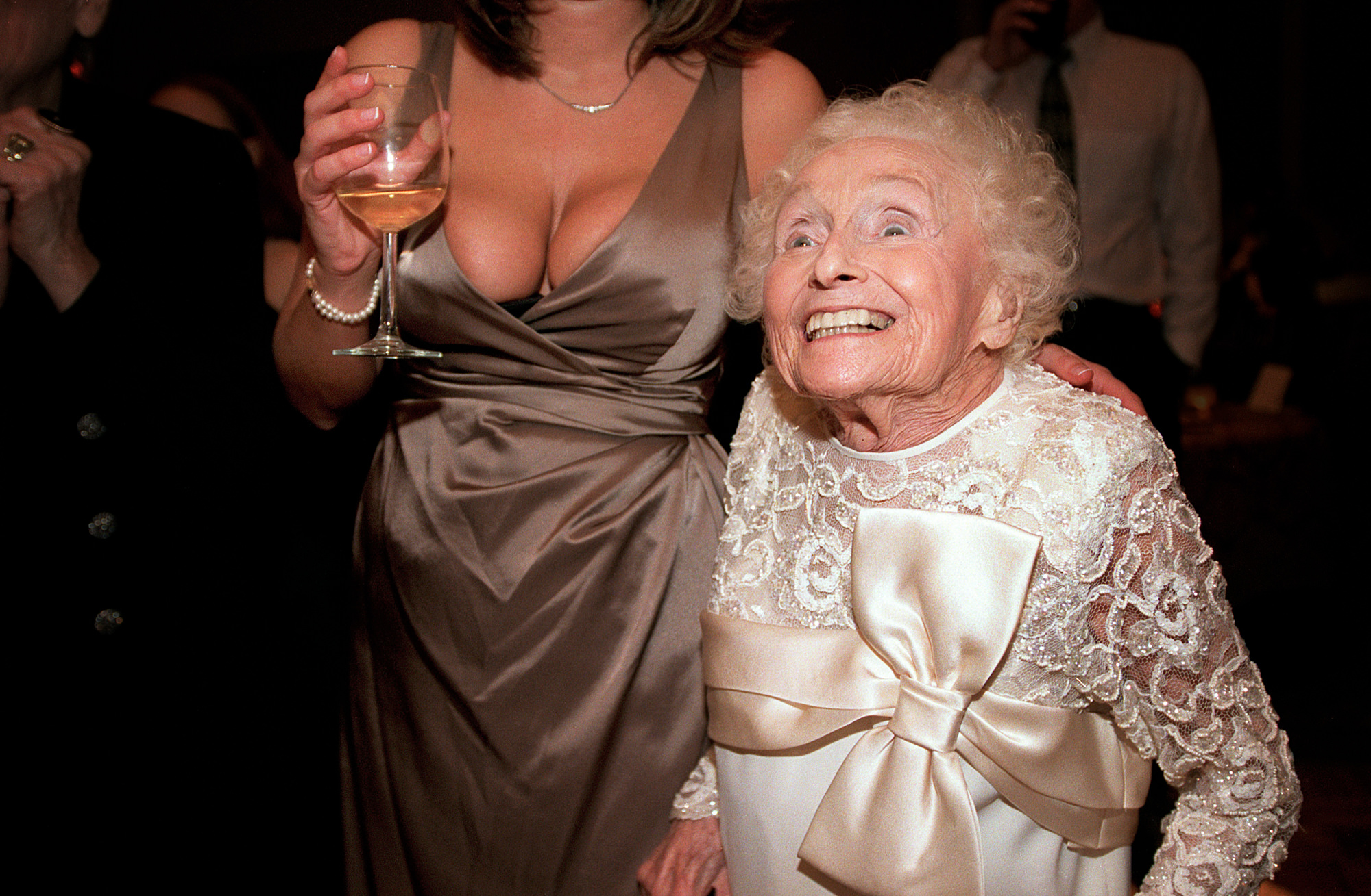 Smiling grandma on dance floor eye level with bridesmaids breasts - photo by Jerry Ghionis