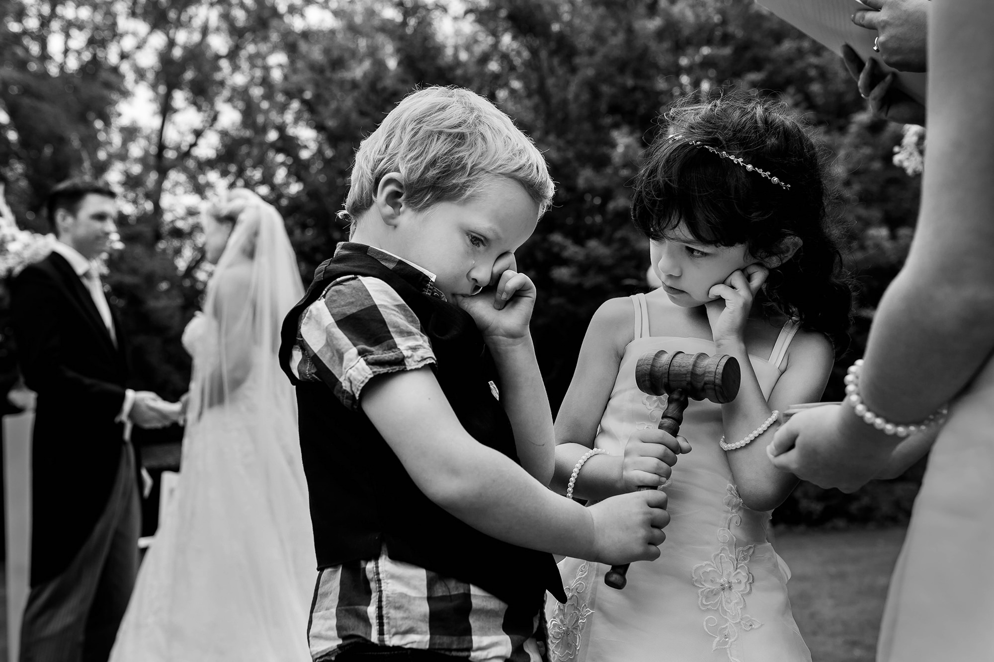 Little kids holding mallet with bride and groom in backgroung photo by Fotobelle: Isabelle Hattink