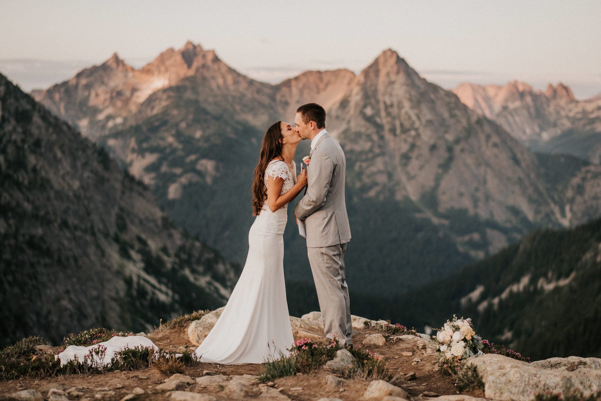 Sweet kiss, bride in lace dress and groom in grey suit- photo by Nick + Danee