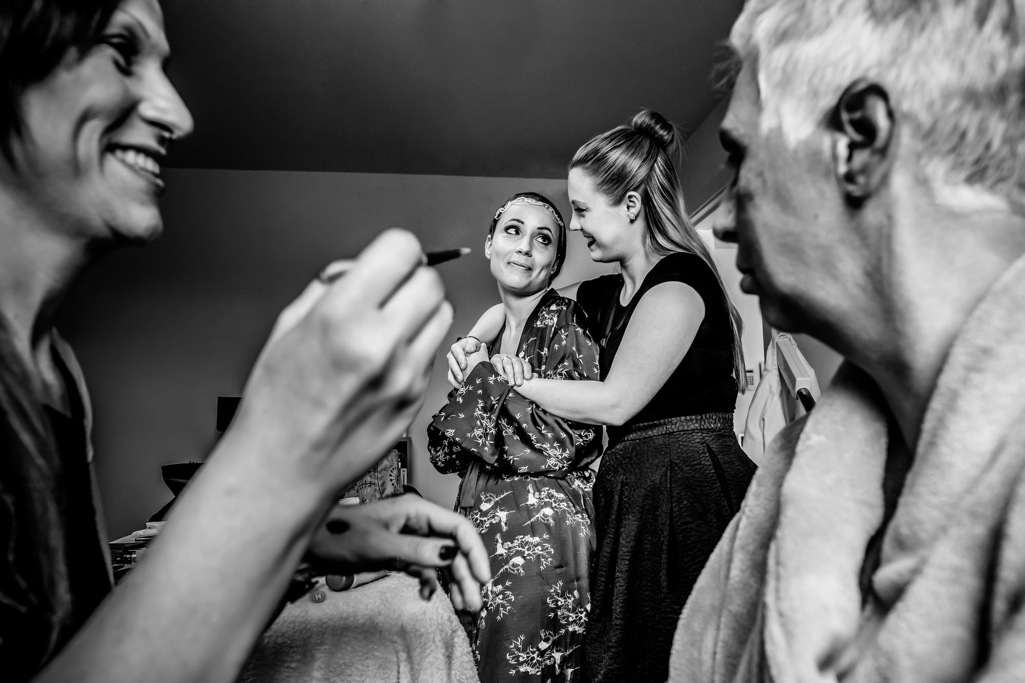 Friend hugs bride while getting ready  - photo by Phillipe Swiggers