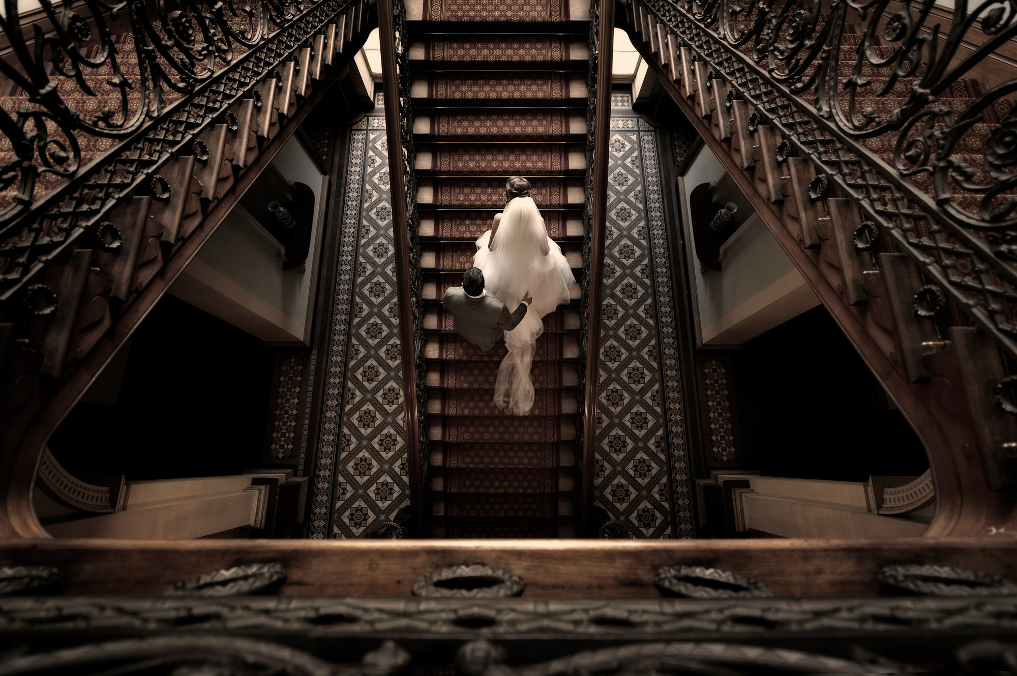 Photo of couple ascending hotel stairs - photo taken from above by Jerry Ghionis