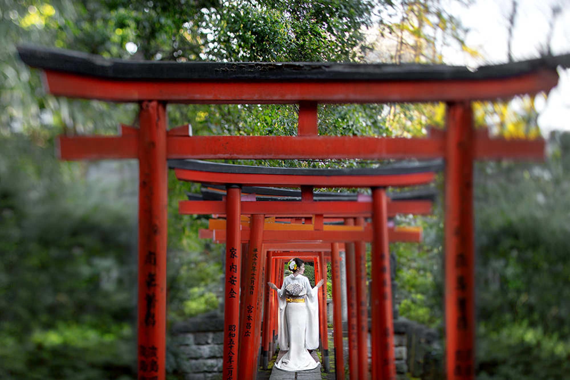 Bride in white silk kimono under traditional Asian arbor