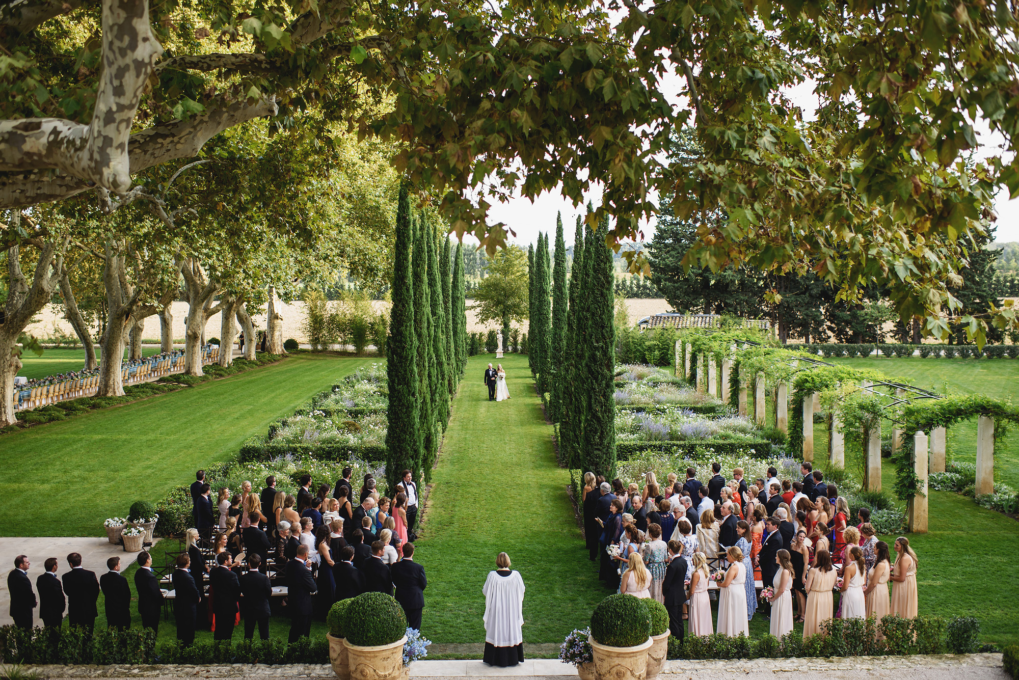 guests await bride walking down garden aisle - photo by Ross Harvey