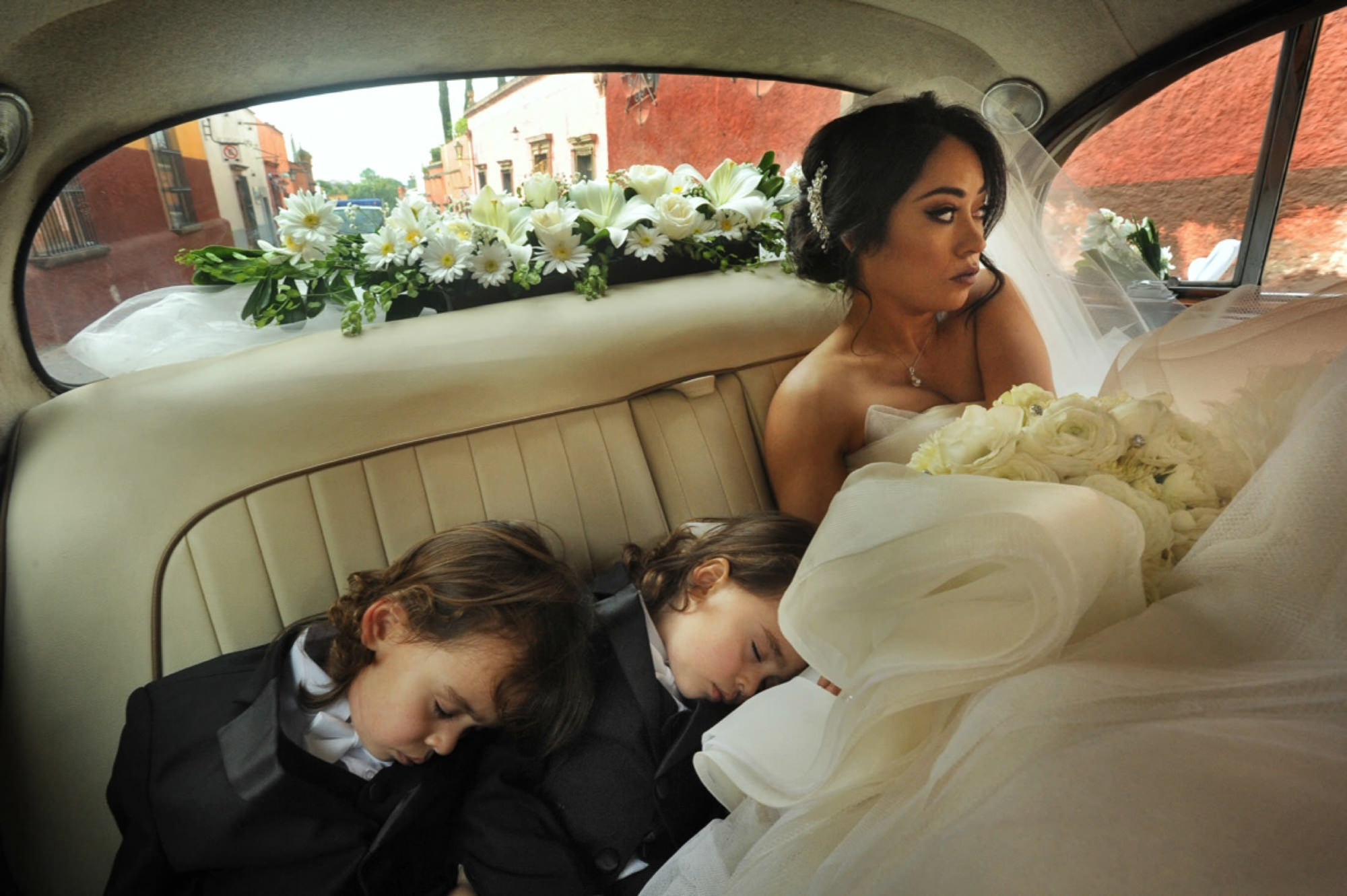 Twins fast asleep in back of car with mom bride - Daniel Aguilar Photographer