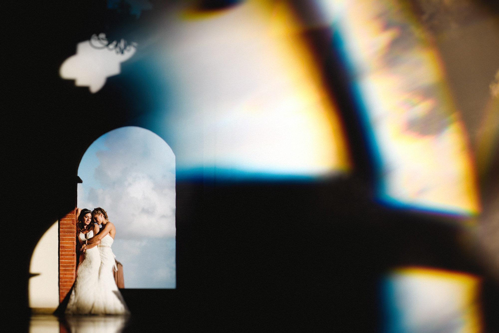 Two brides embrace in strapless gowns - prism photo by Fer Juaristi