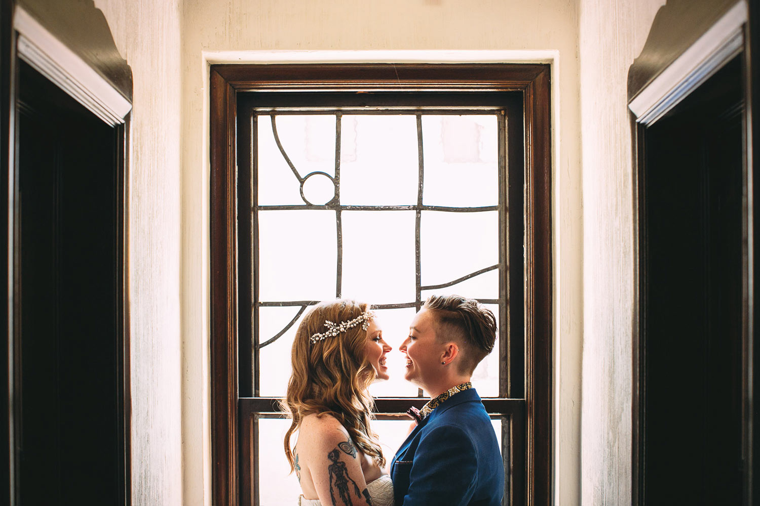 Joyful brides smiling at each other in front of window, by Callaway Gable