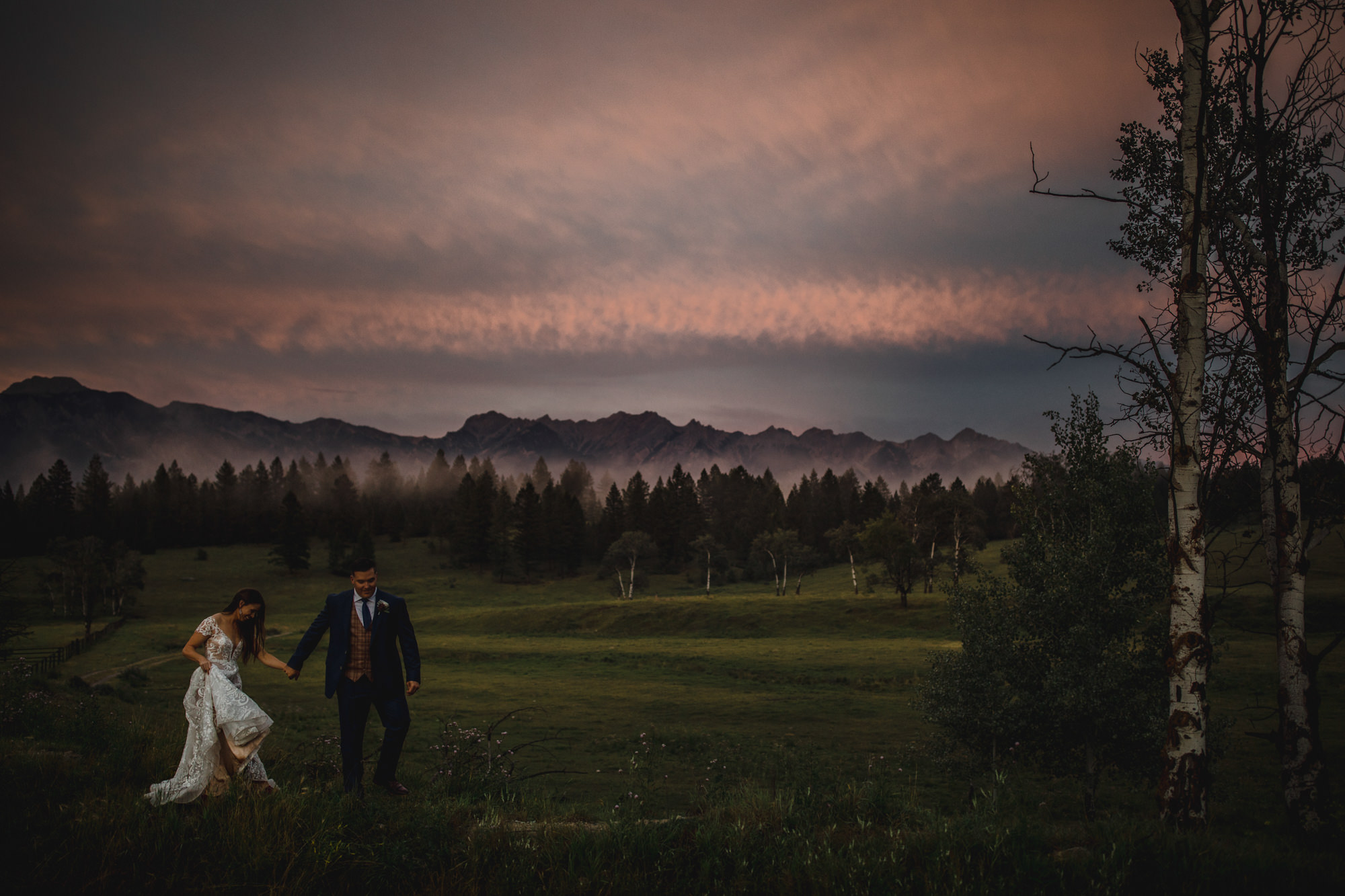 Couple in front of pink clouds and mountains - photo by McClintock Photography Agency