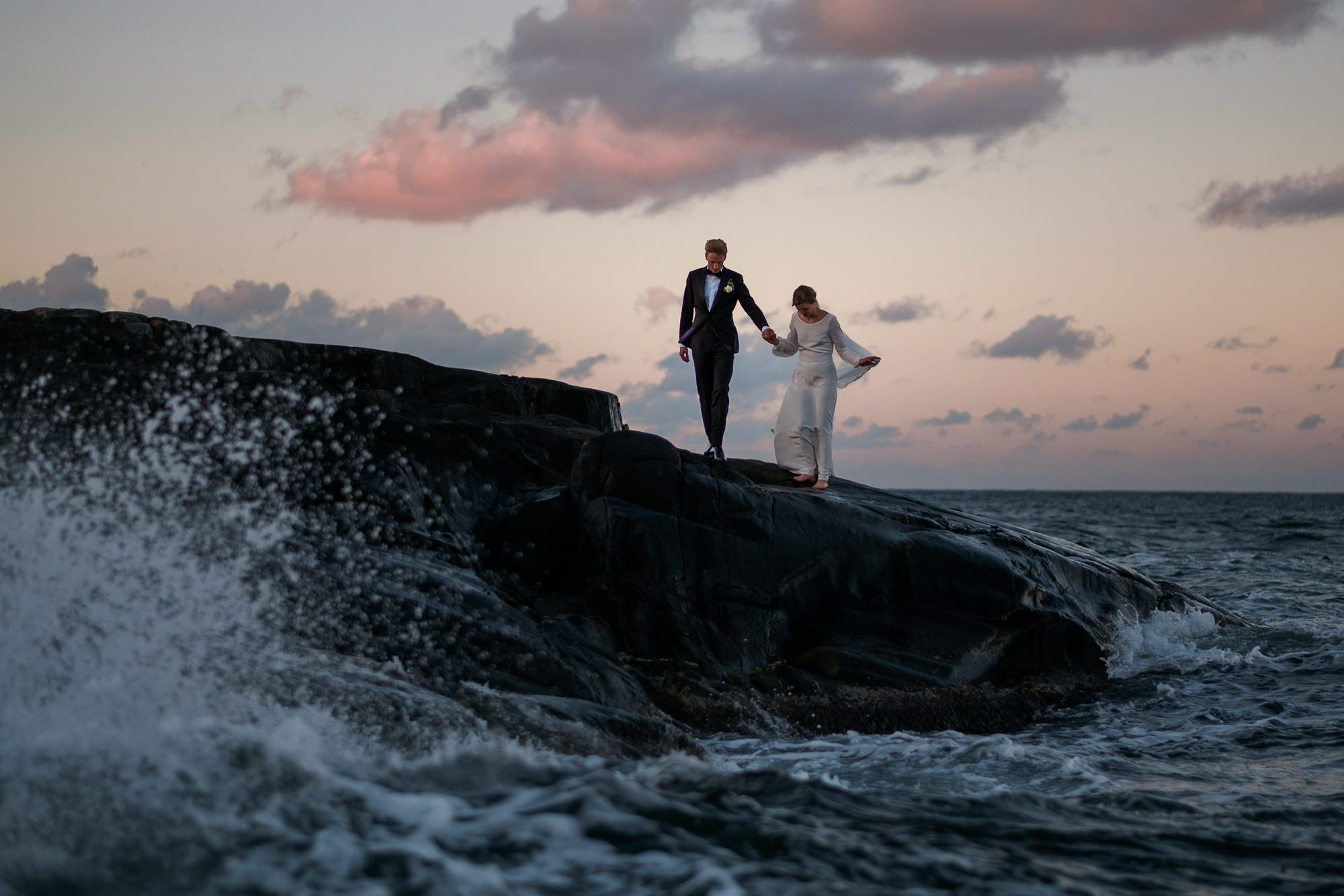 Wave crashes as couple walks on rocky beach photo by Nordica Photography