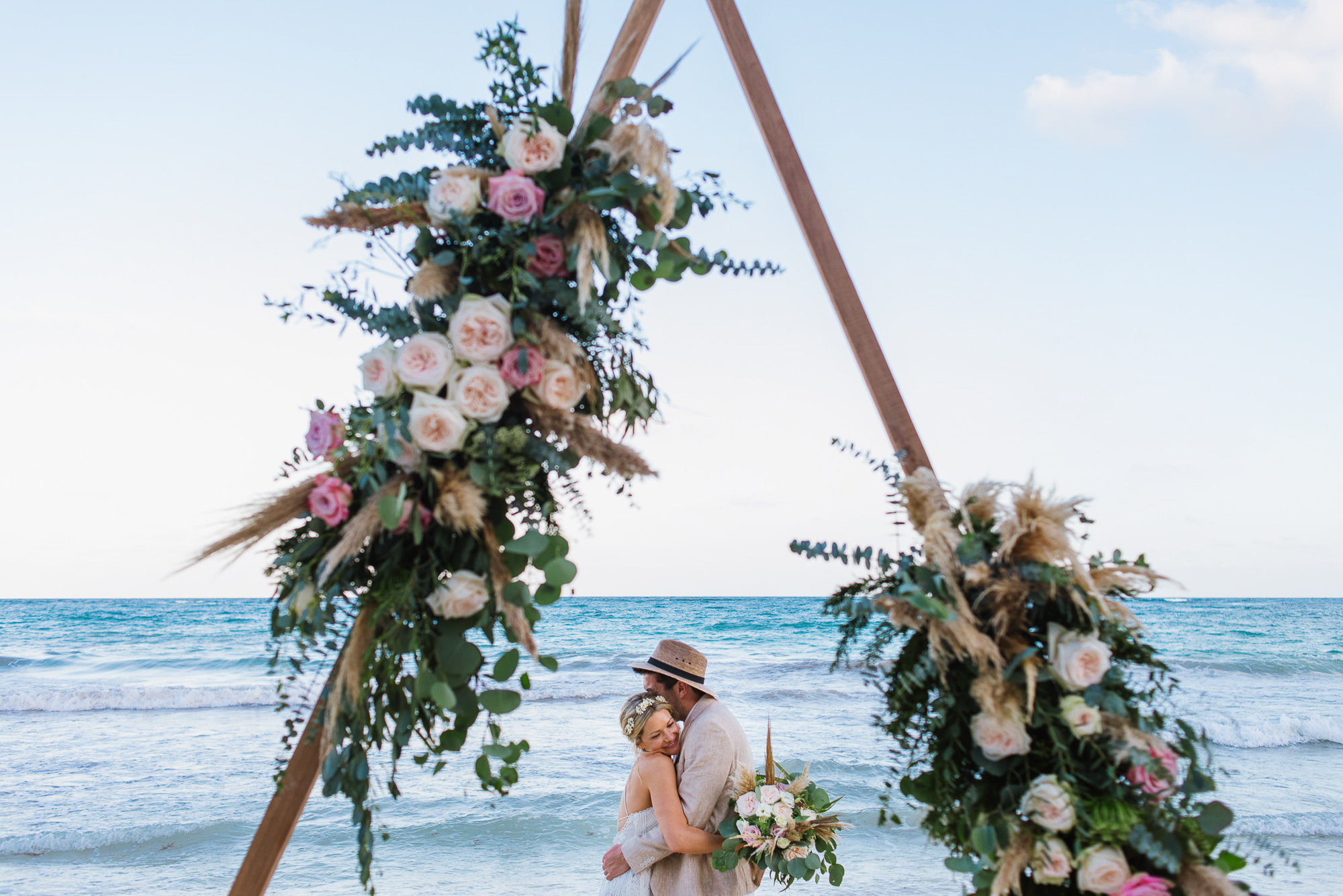Newlyweds hug with triangle arbor in foreground, by Citlalli Rico