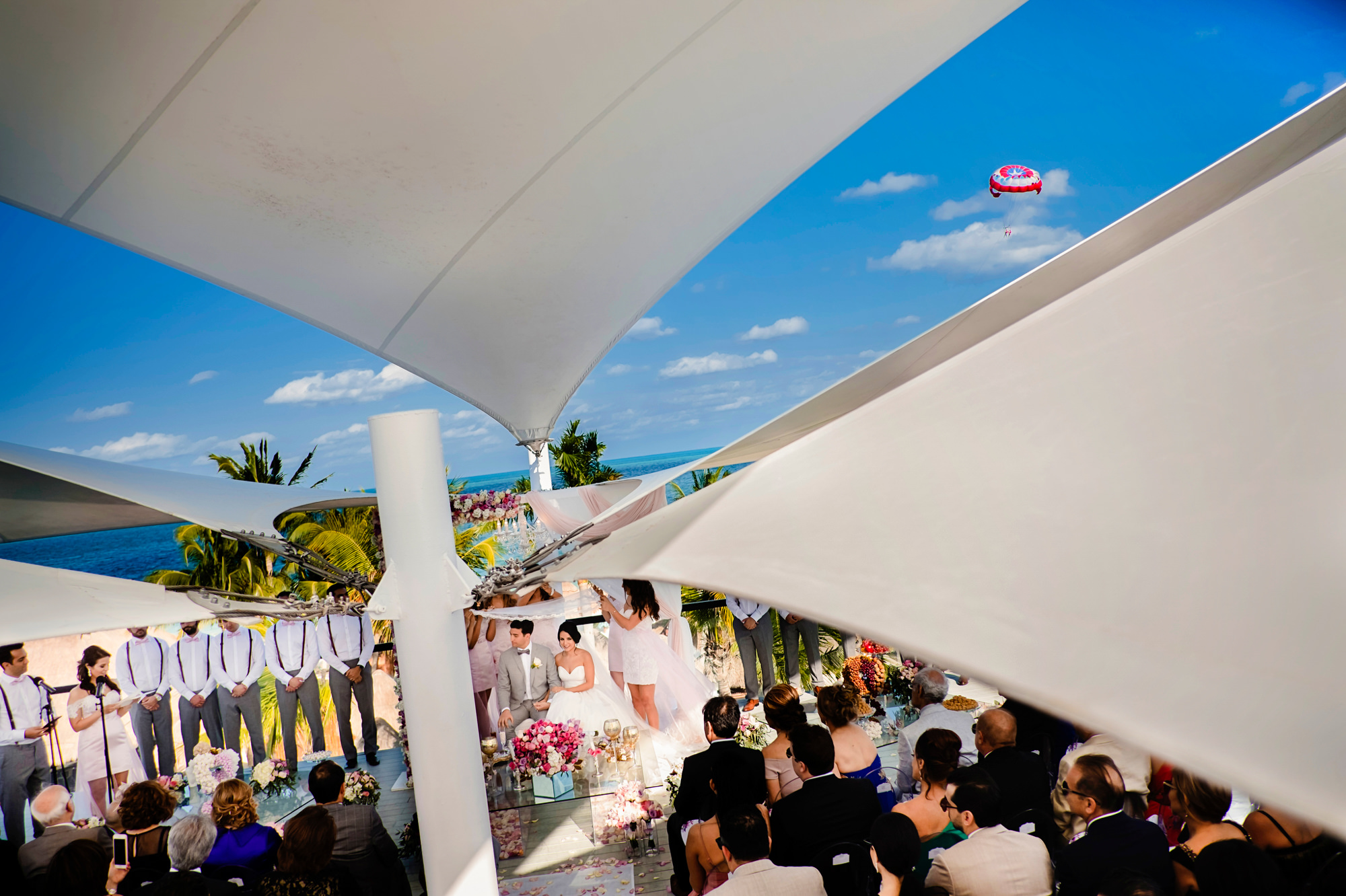Unique composition of wedding ceremony beneath tents with parachute in background by Chrisman Studios