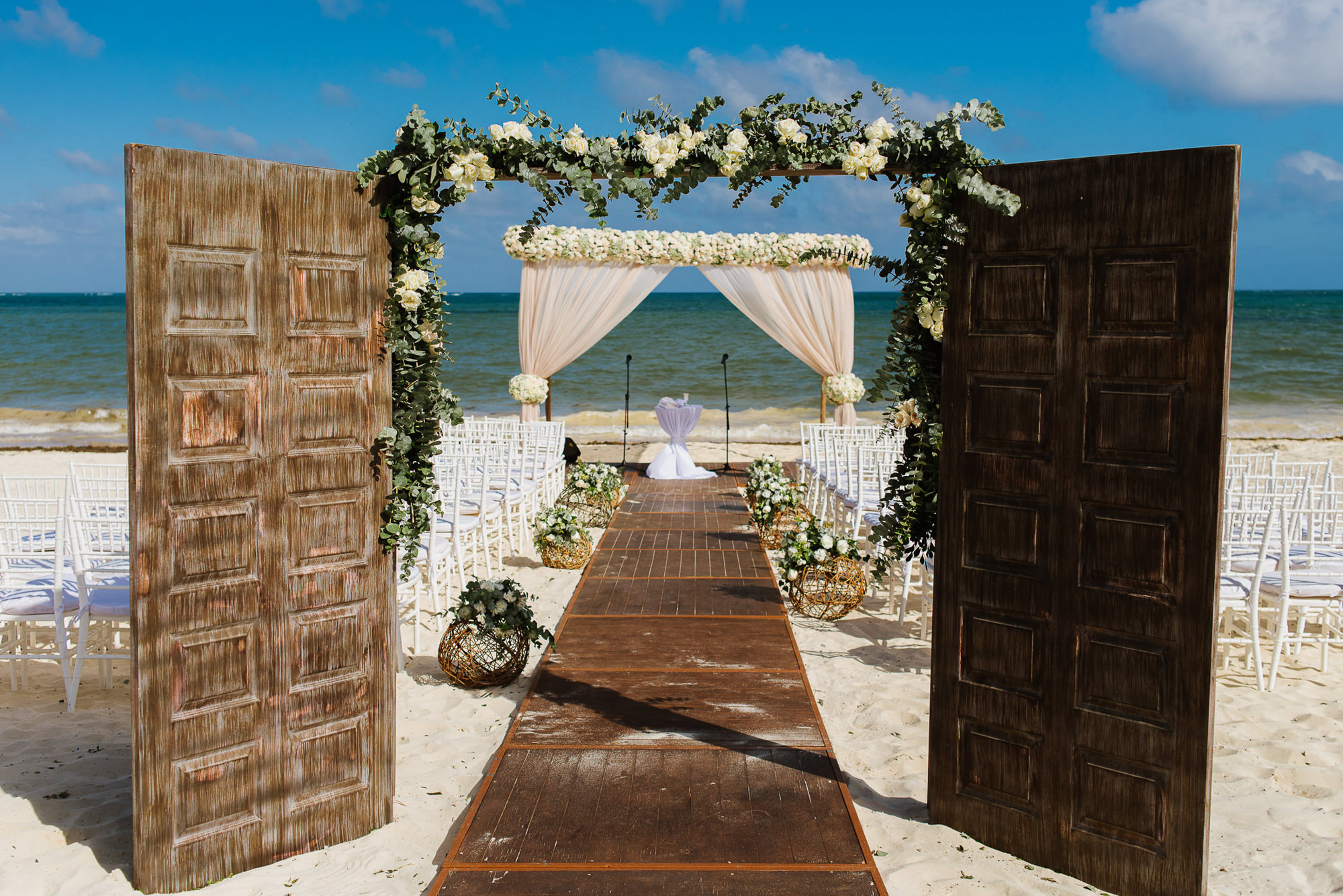 Ceremony decor at the beach with doors and white floral arbor, by Citlalli Rico