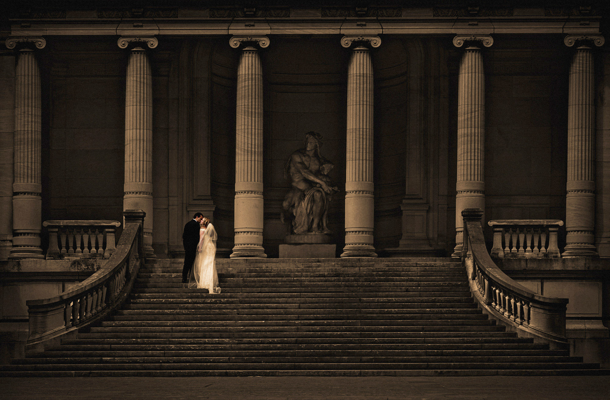Wedding couple on staircase with columns - photo by Jerry Ghionis