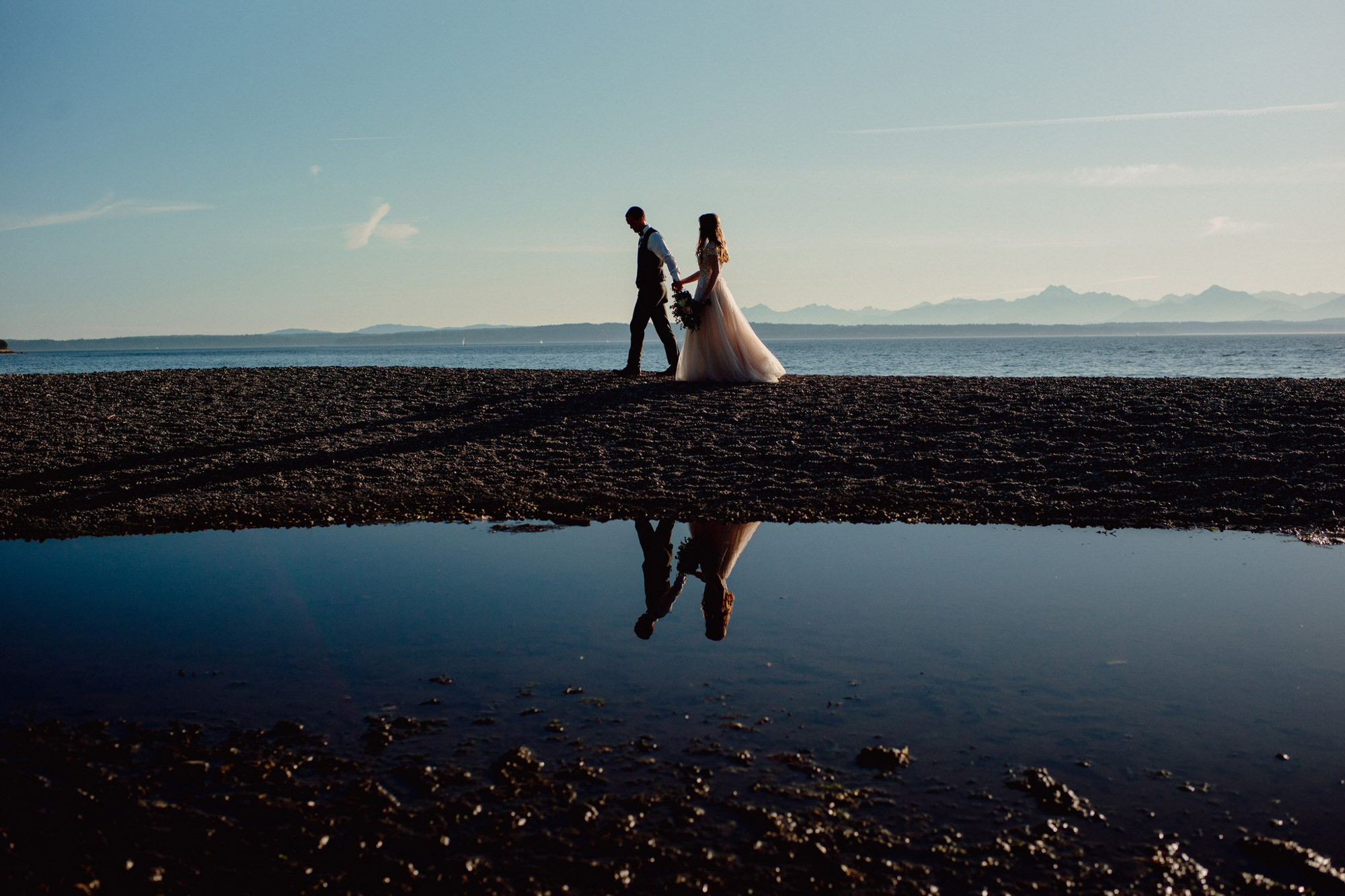 bride and groom walking on Puget Sount beach - photo by Benj Haisch