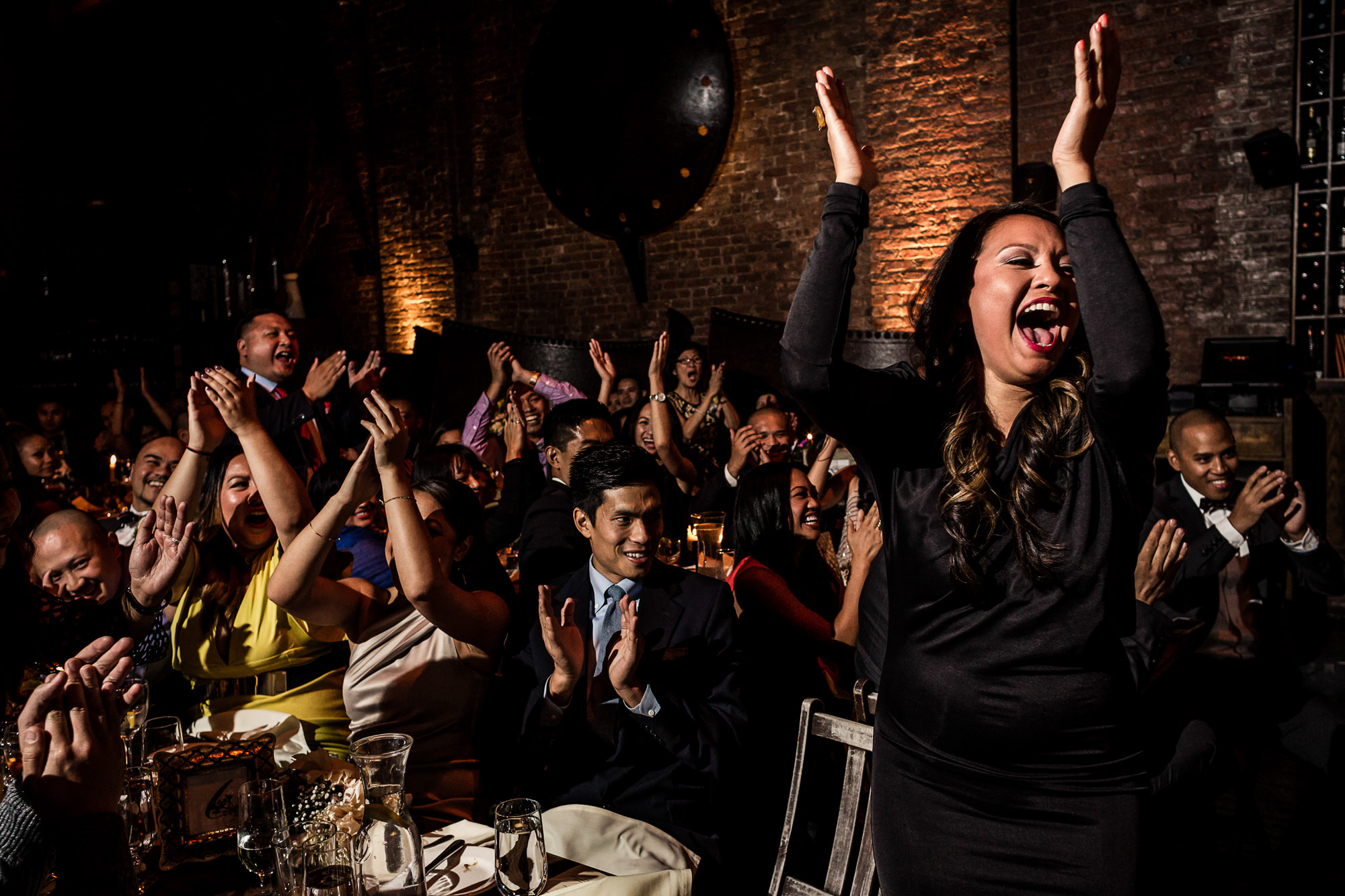 Jubilant wedding reception guests clapping - photo by Jag Studios
