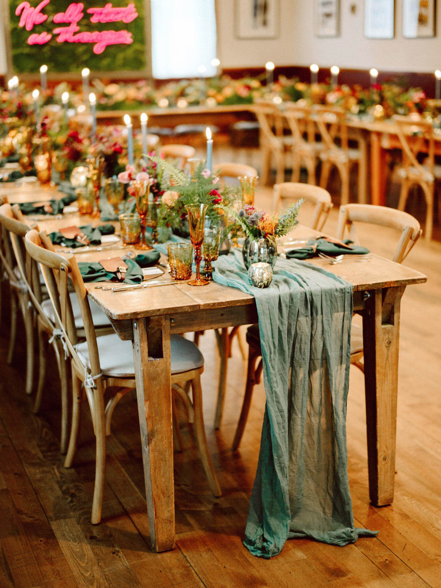 Wedding reception with green table runner and amber glass - Photo by Benj Haisch