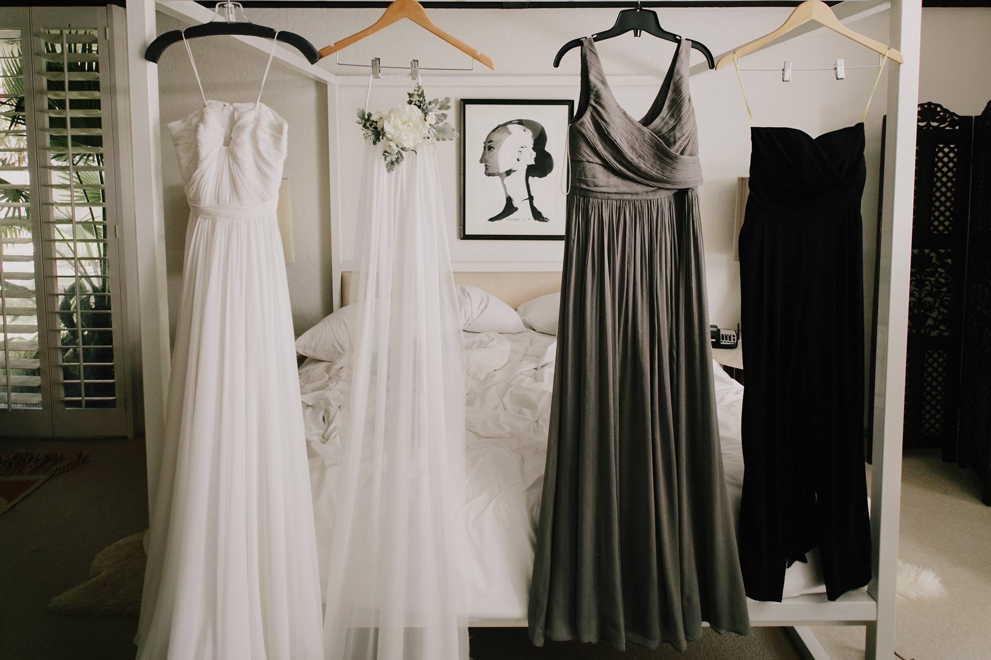 Grey and white bridal trousseau hanging on bed - photo by James Moes