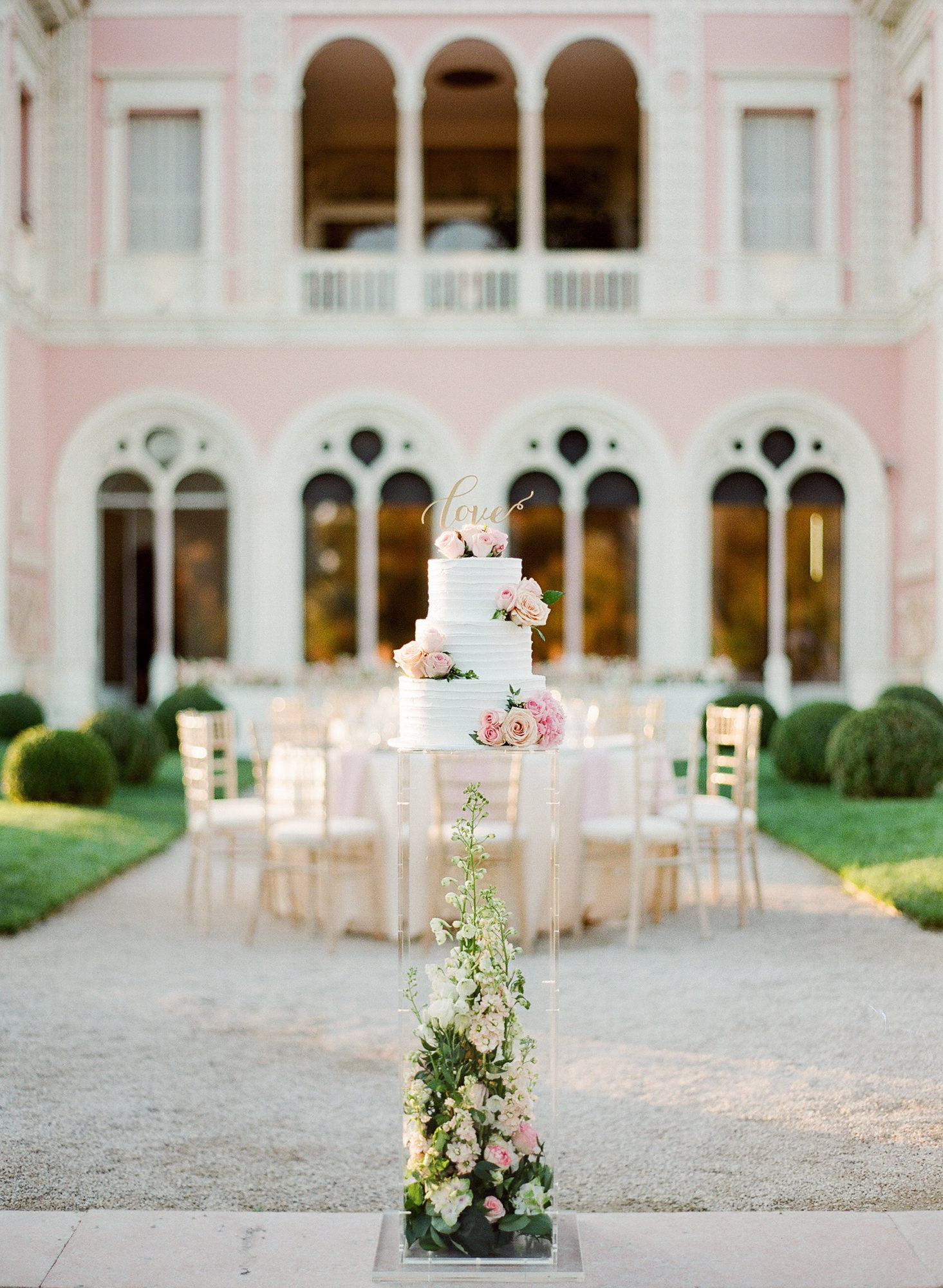 White buttercream cake with roses on pink table at pink villa - Greg Finck Photography